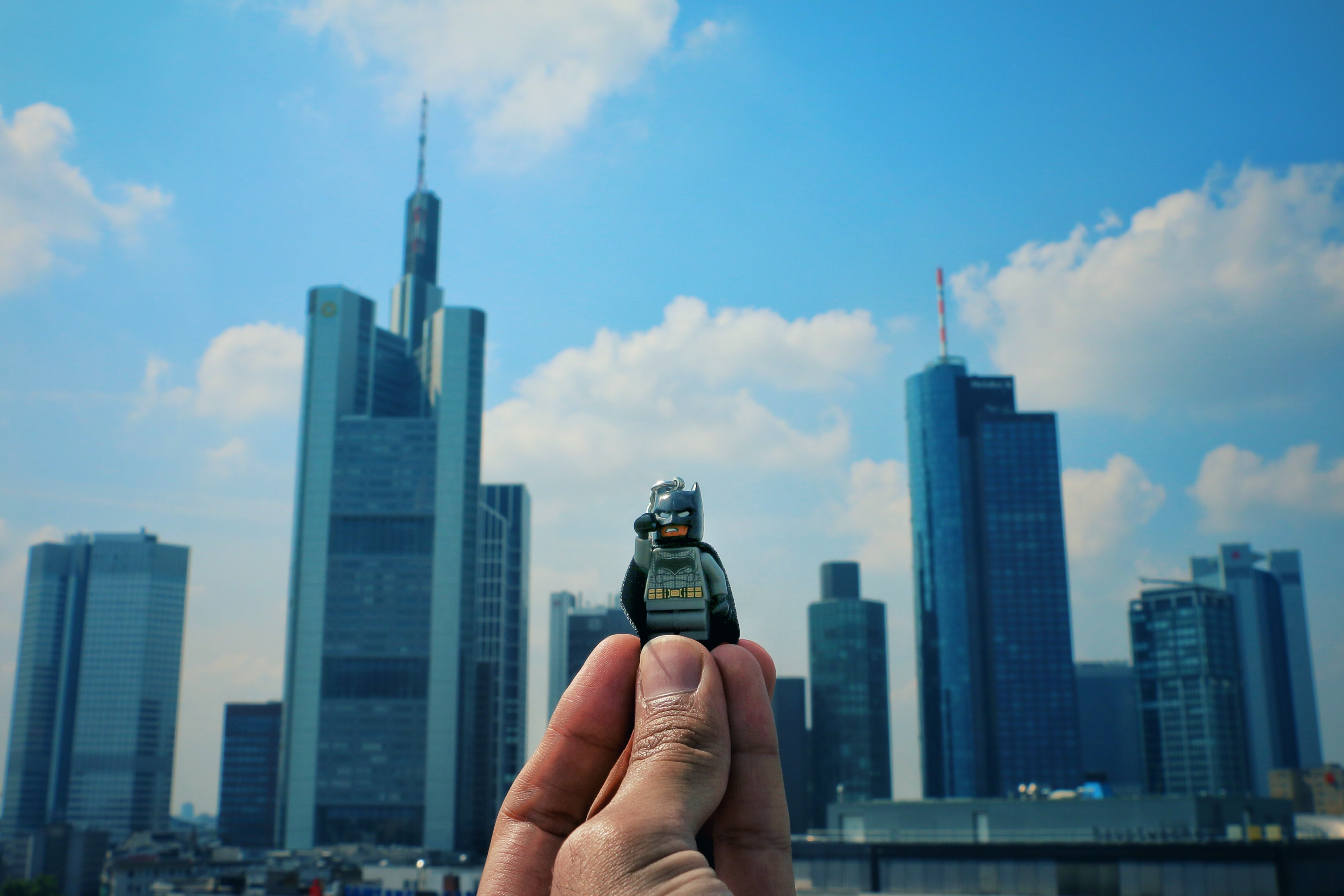A person holding a Lego guy toy in the air with his fingers, with skyscrapers and a cloudy sky in the background.