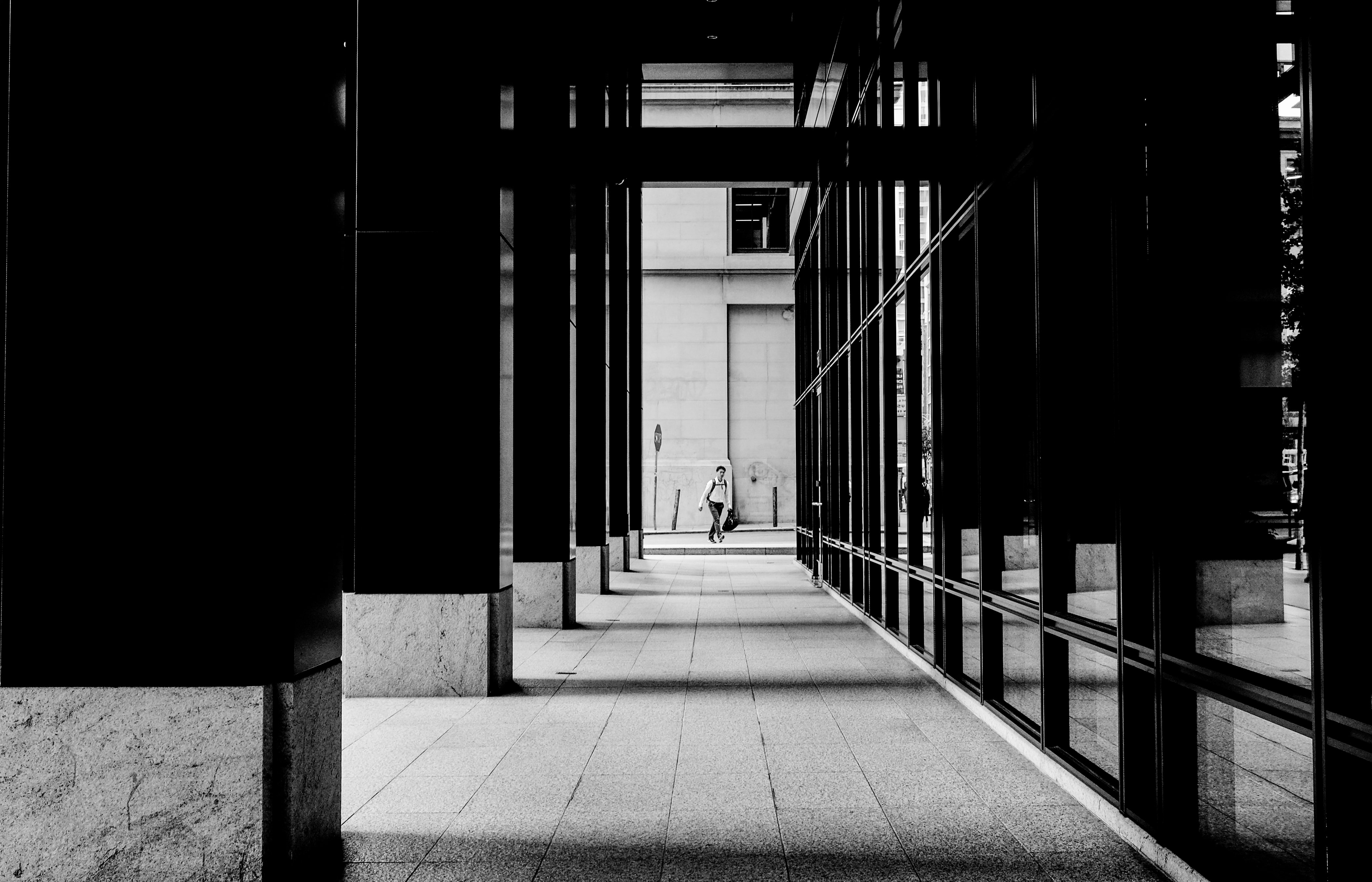 Black and white long shot of man crossing road through outdoor corporate hallway in San Francisco