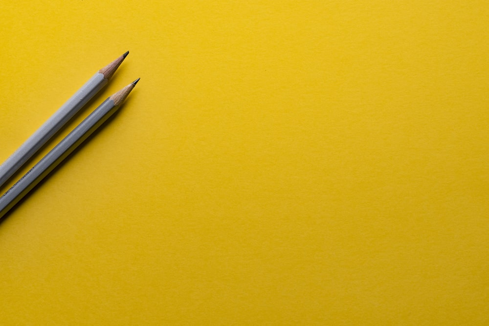 two gray pencils on yellow surface