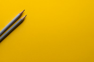 two gray pencils on yellow surface paper zoom background
