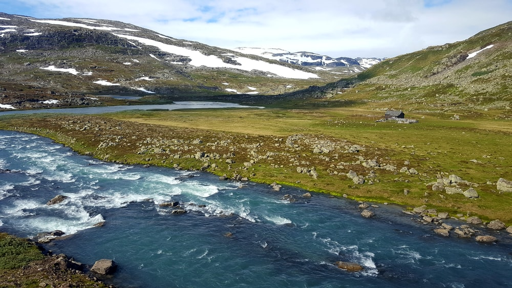 aerial photography of winding river between snowy mountains
