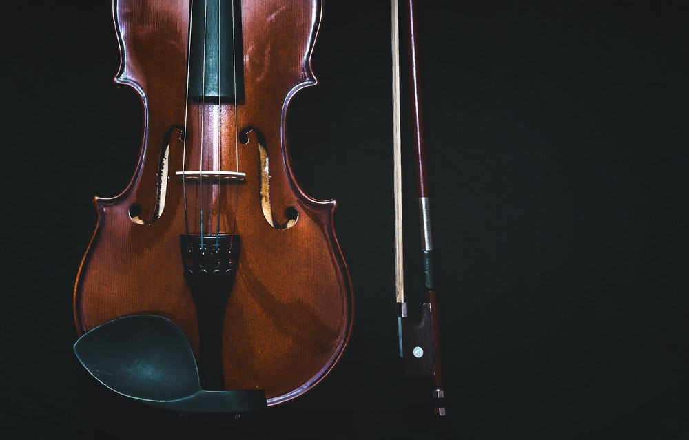 brown violin with bow in black background