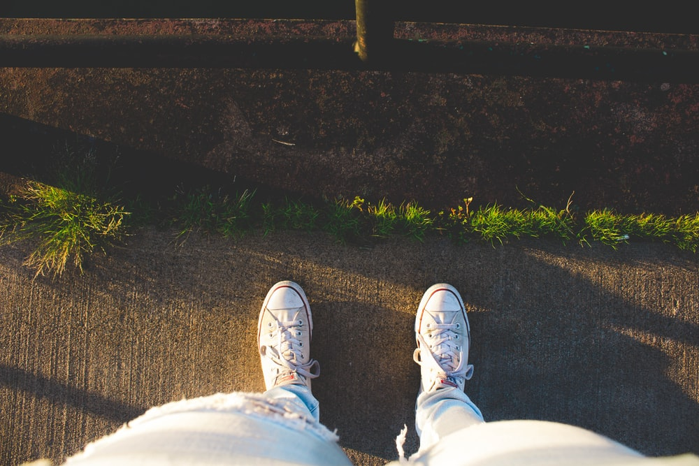 person wear sneakers standing on road