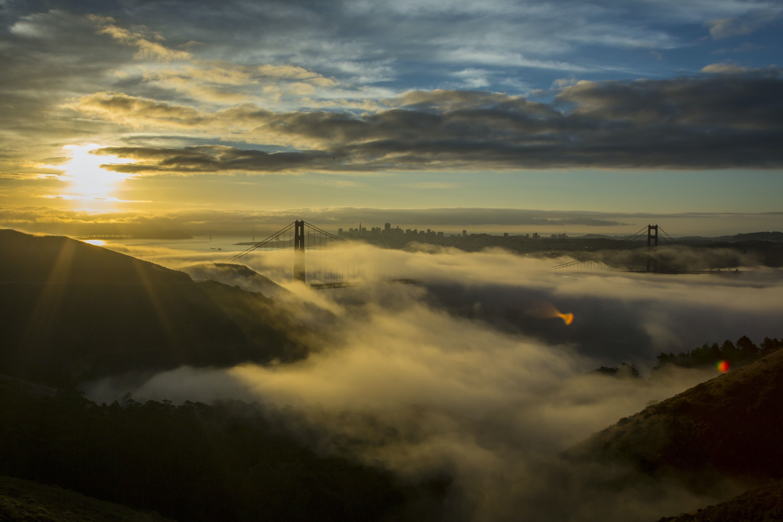 San Francisco's Golden Gate Bridge covered in fog, the sun in a cloudy sky