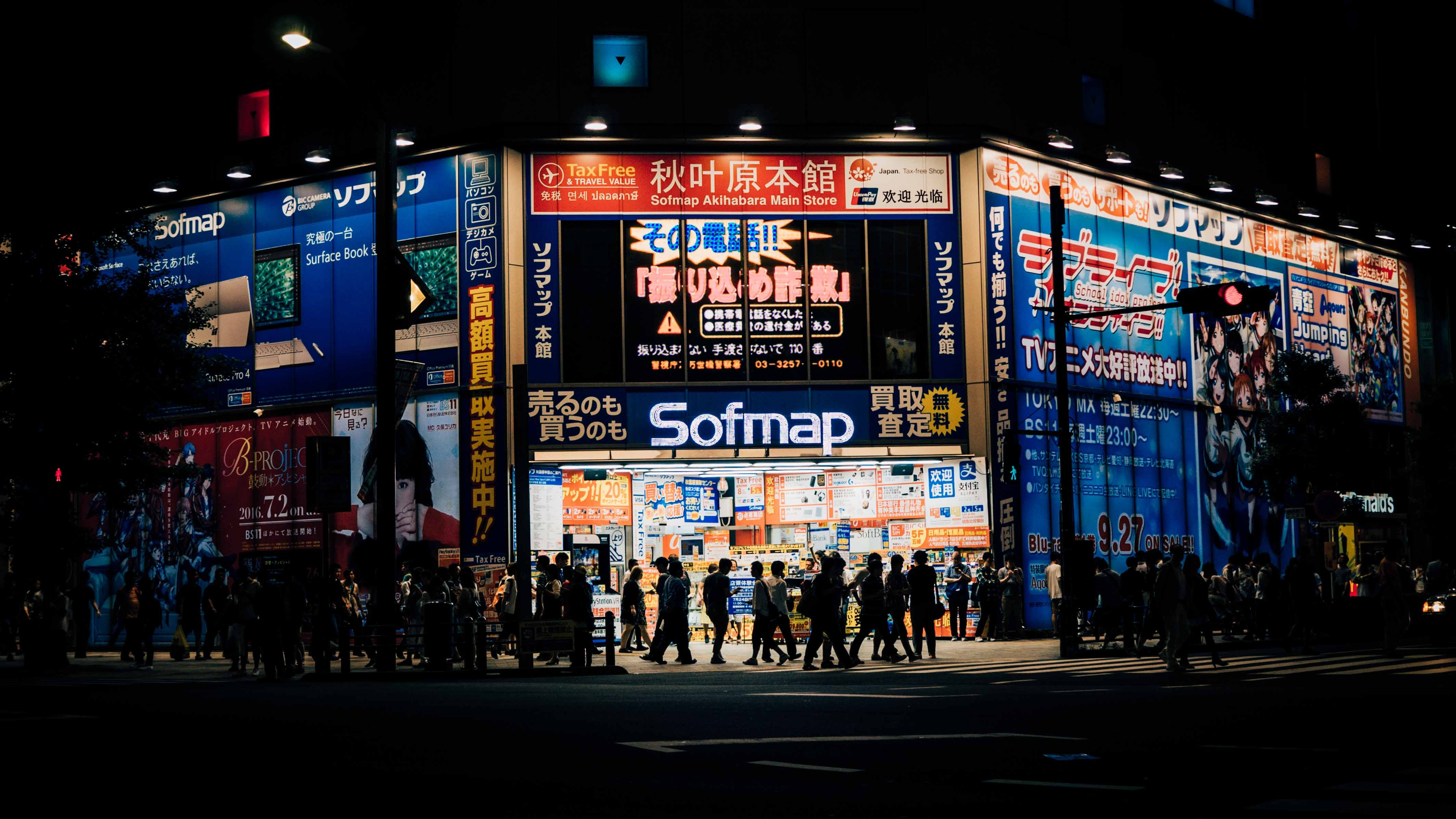 Silhouettes of pedestrians crowding in front of a building covered with advertisements