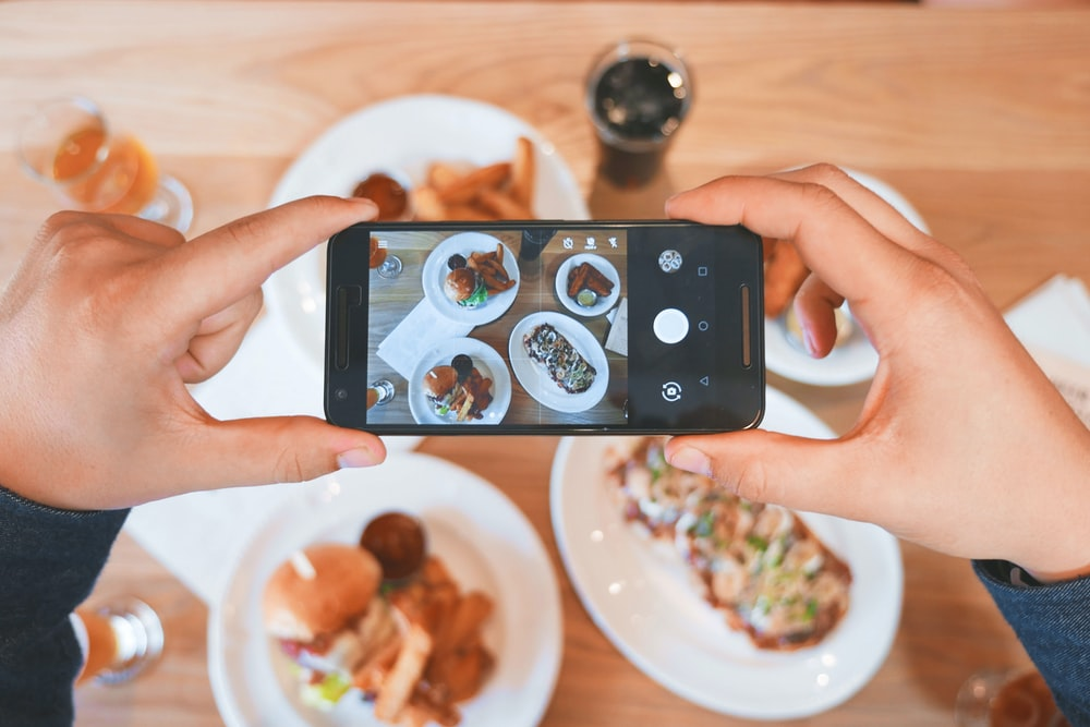 Person takes a picture of their brunch on their smartphone