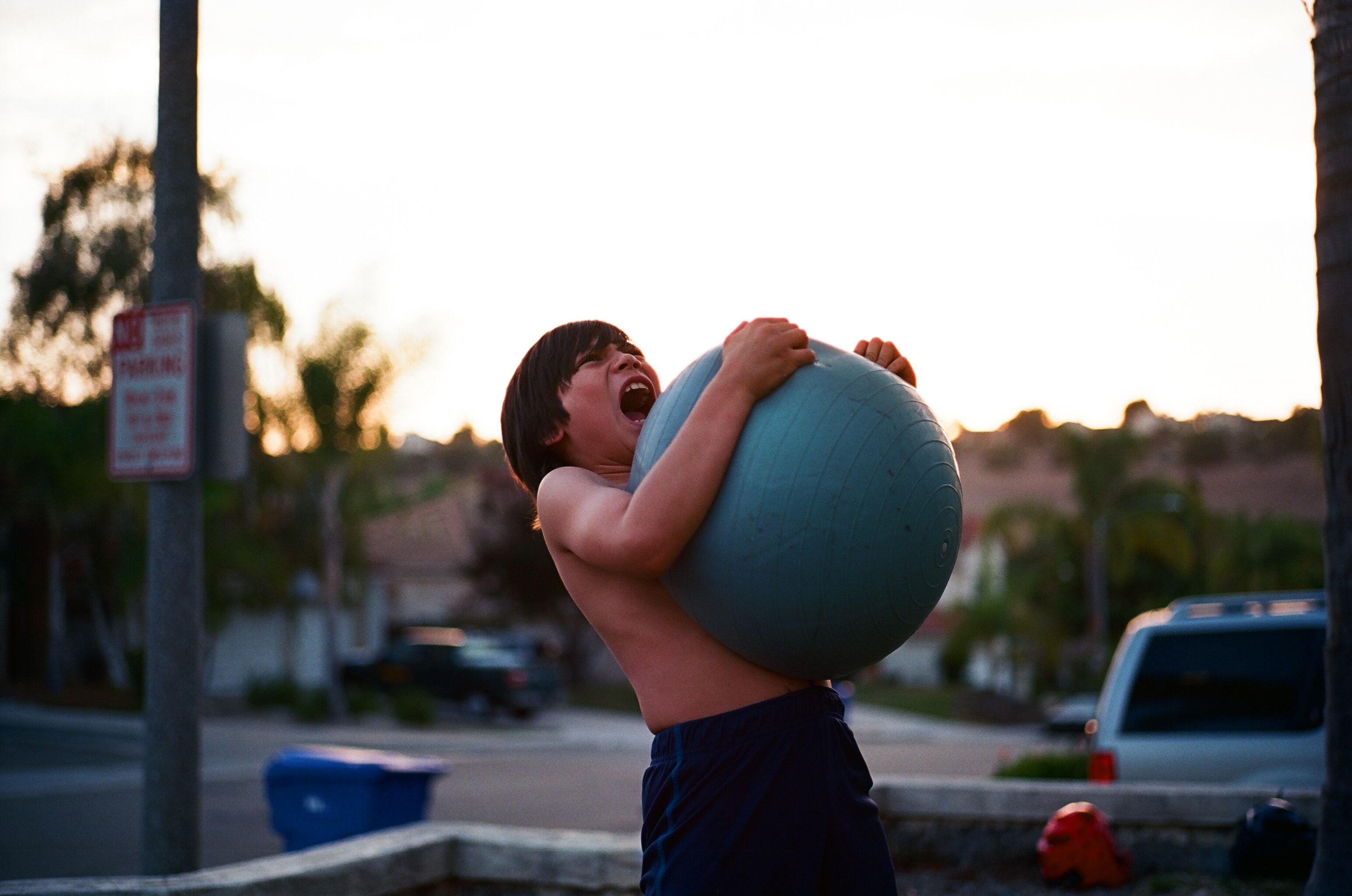 Shirtless boy squeezing and playing with large inflatable ball near parked car in Oceanside