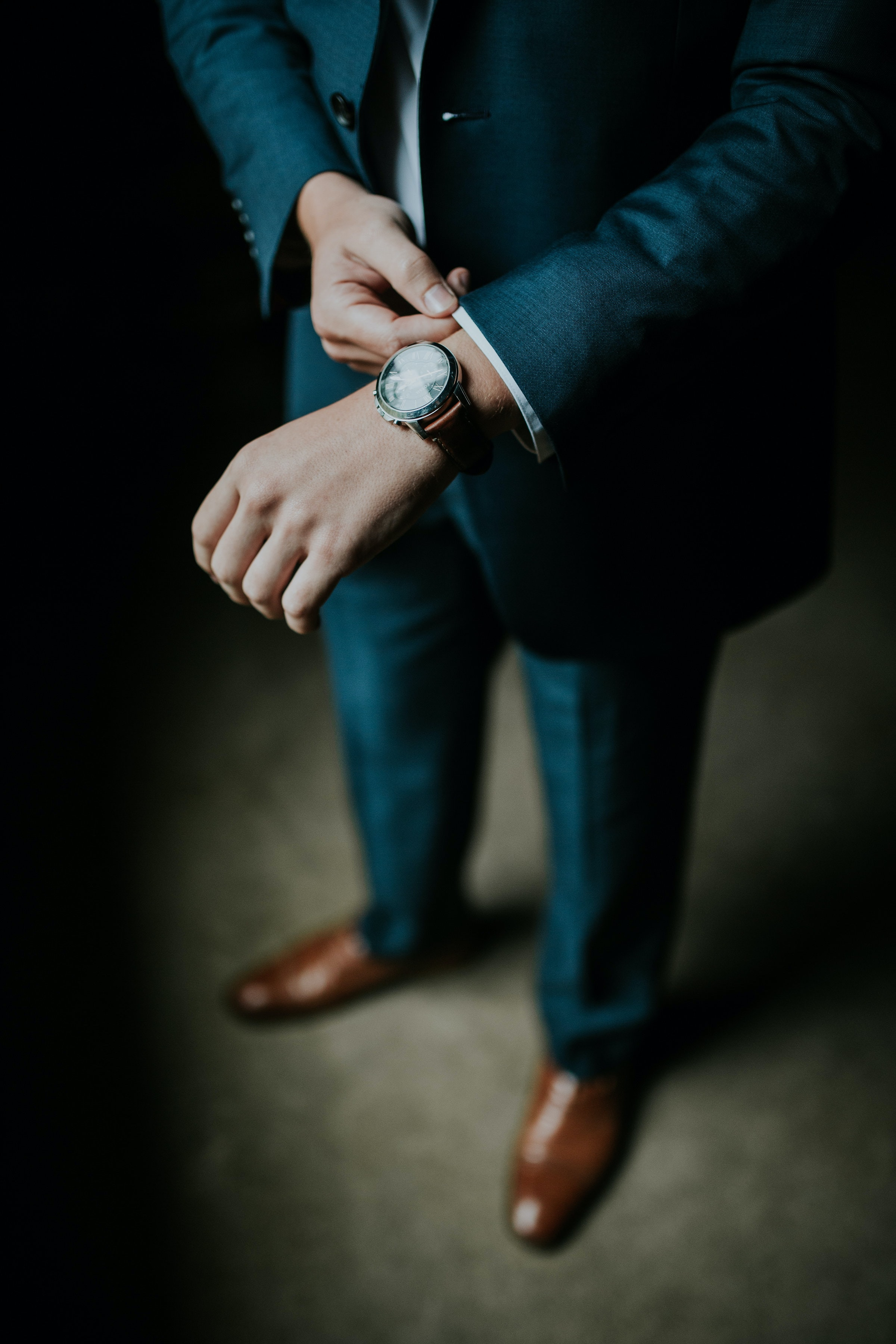 A man in an elegant suit adjusting the sleeve of his shirt
