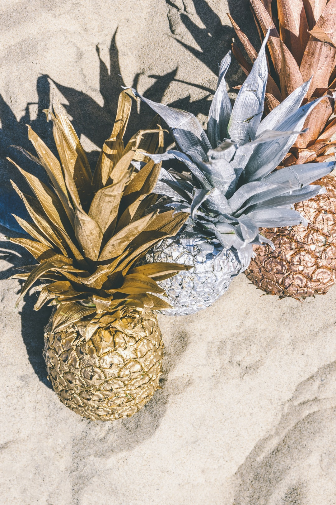 gold, silver, bronze pineapple in sand