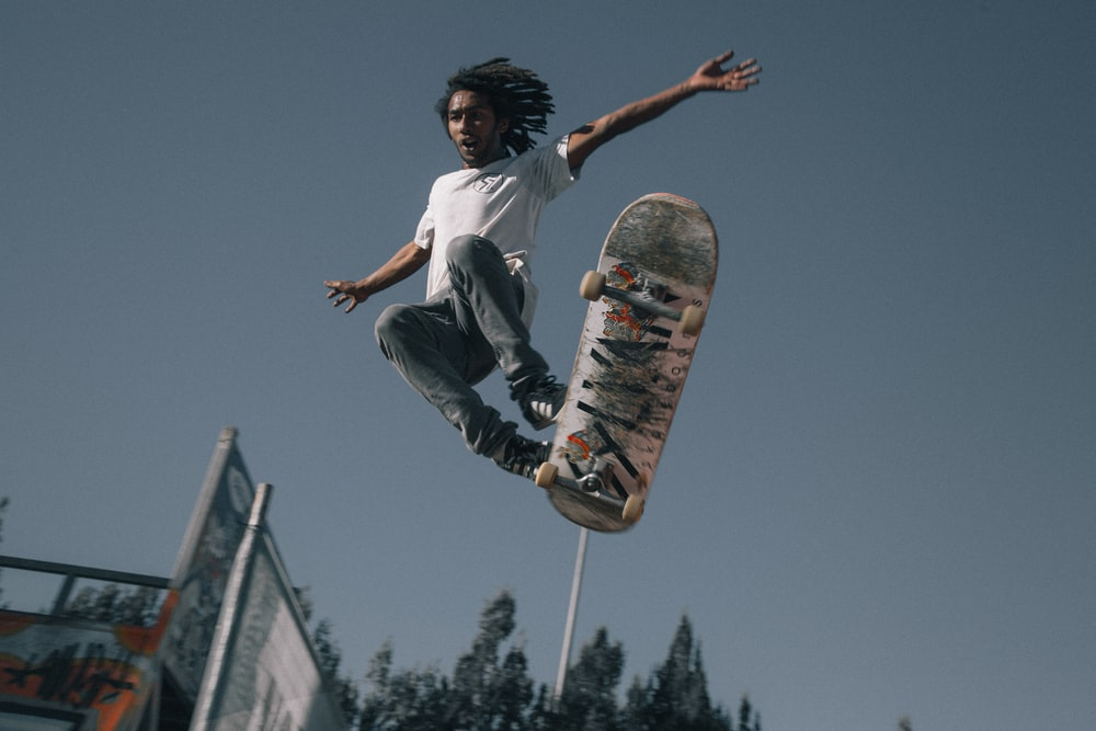 man wearing white T-shirt using skateboard