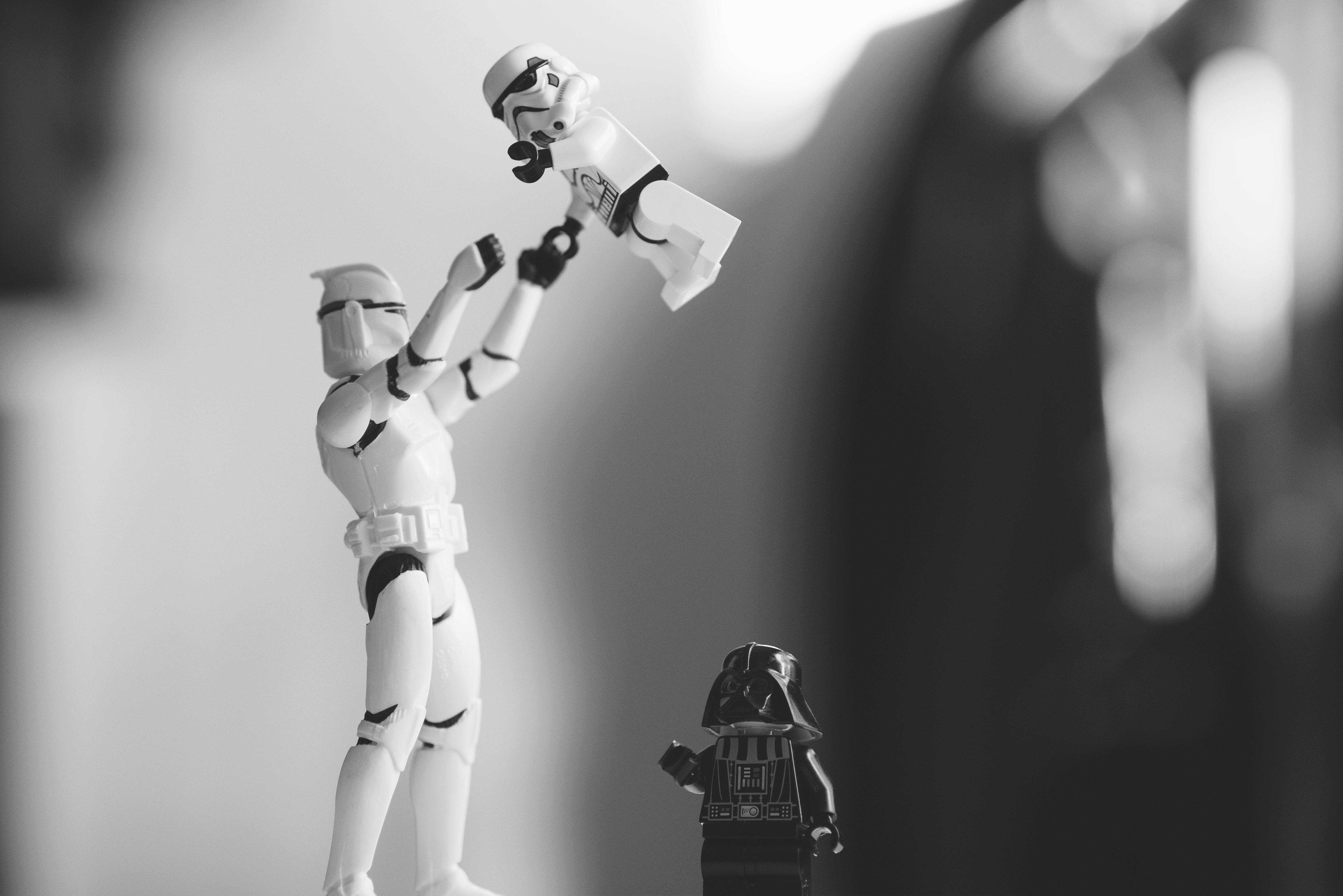 Black and white shot of toy star wars storm trooper and Darth Vader from Star Wars figures in motion