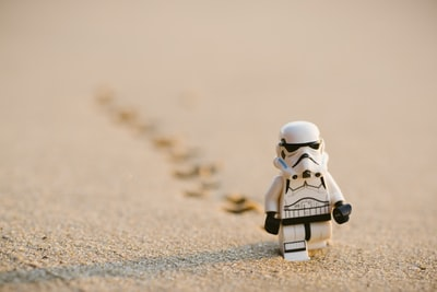 stormtrooper minifigure walking on the sand game teams background