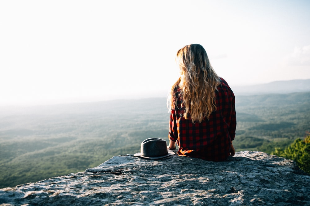 woman wearing red and black gingham shirt sitting on cliff with hat by its side