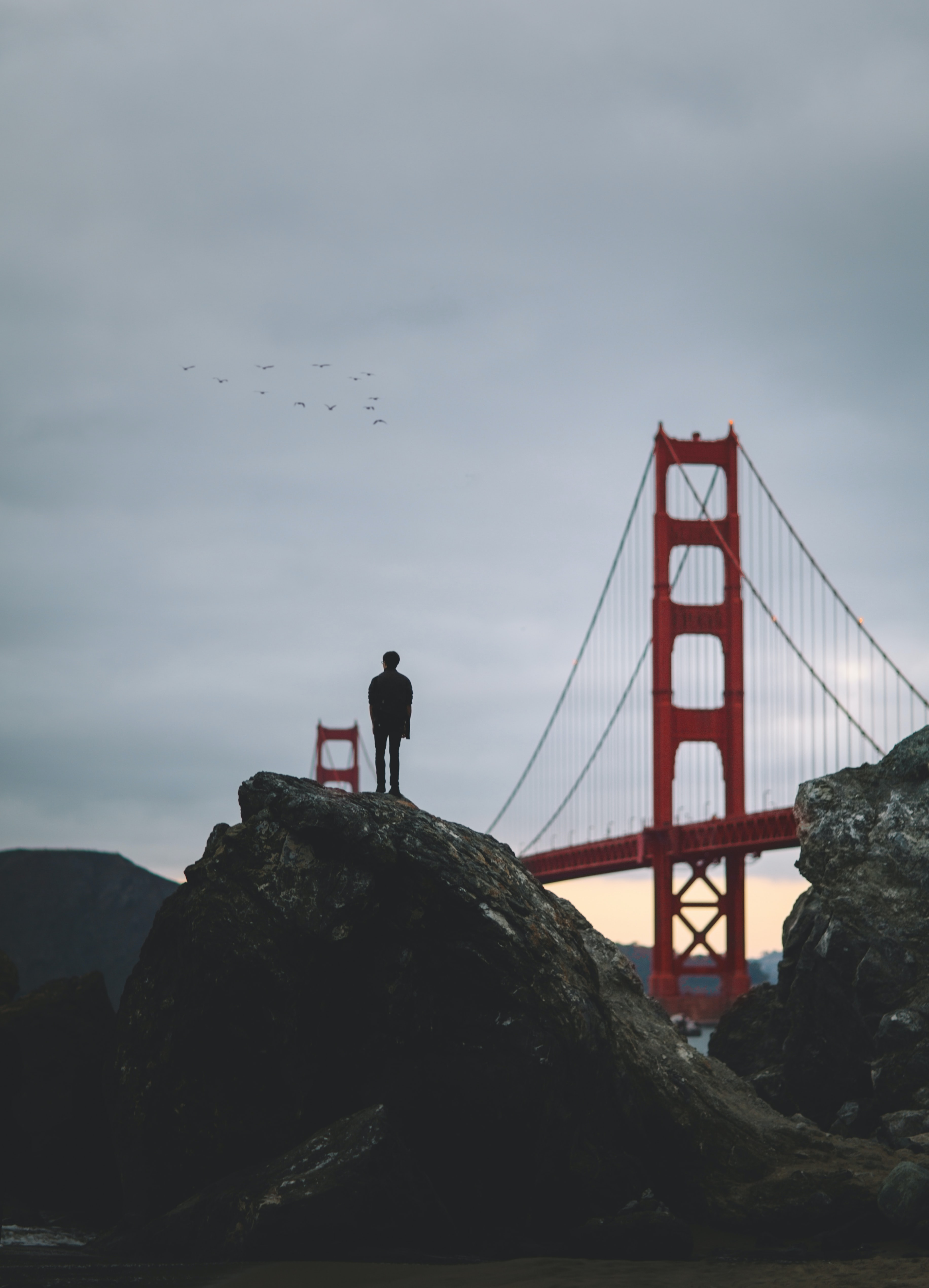 A lone person standing on a boulder, looking towards the Golden Gate Bridge.