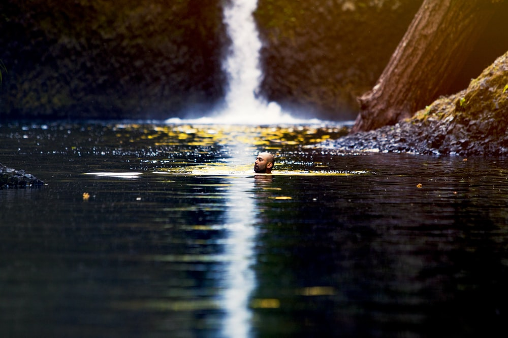 man swimming on waterfall puddle
