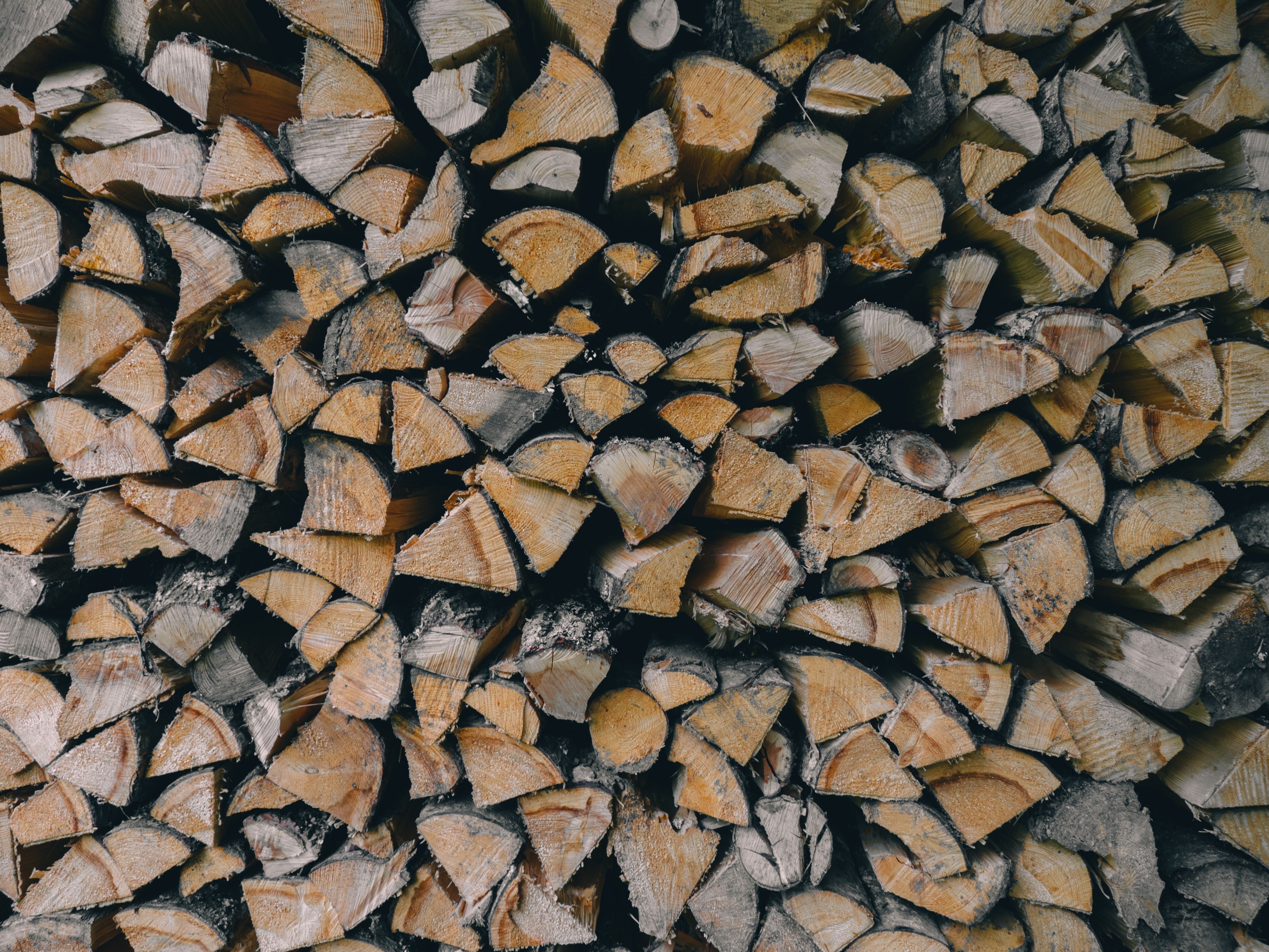A large stack of firewood cut into wedge-shaped pieces