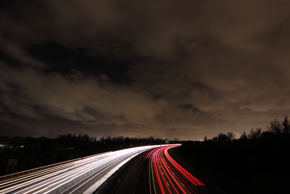 timelapse photography of passing cars on road at nighttime