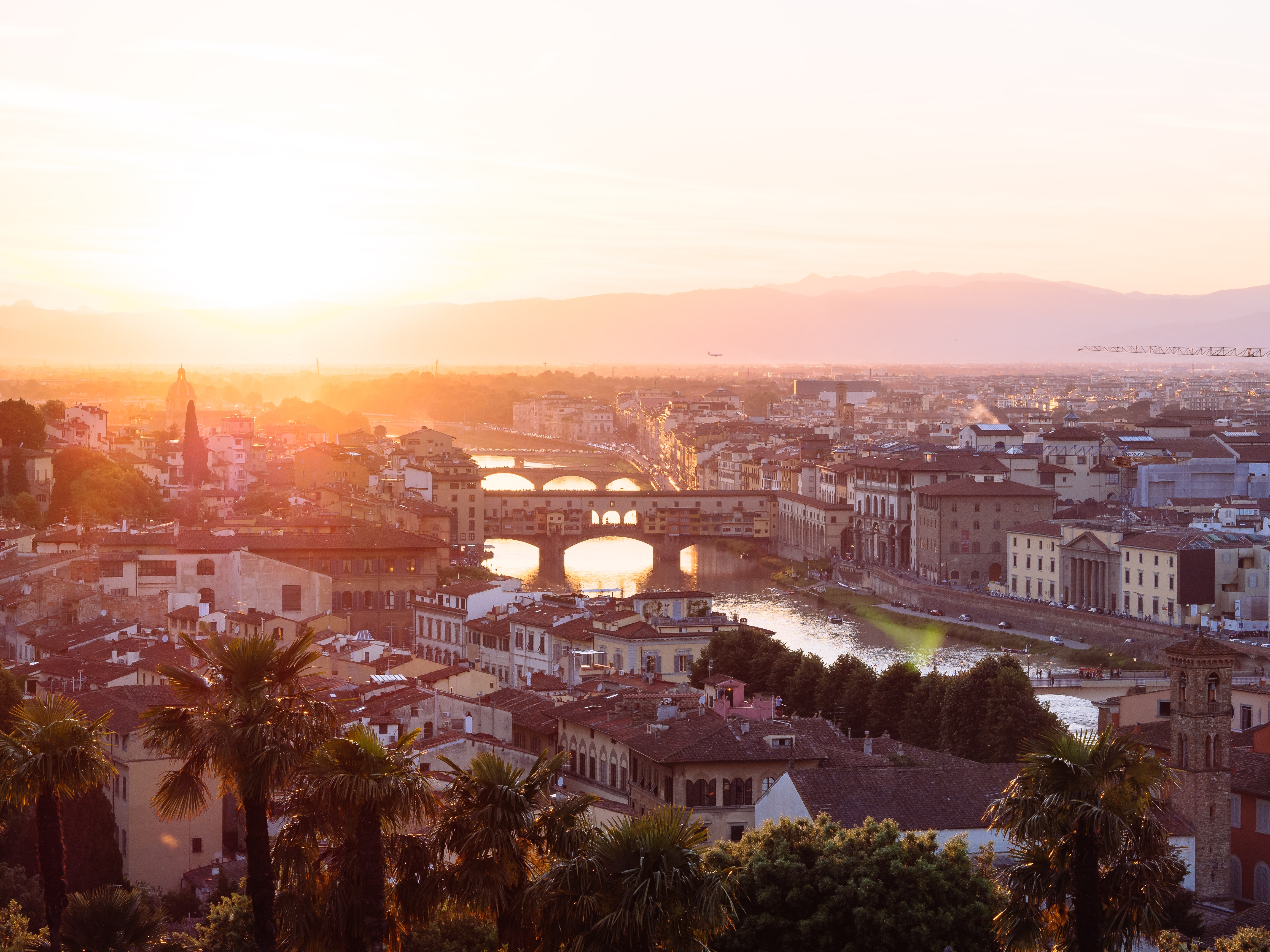 The sun sets over the bridges of the River Arno in the city of Florence, Tuscany, Italy