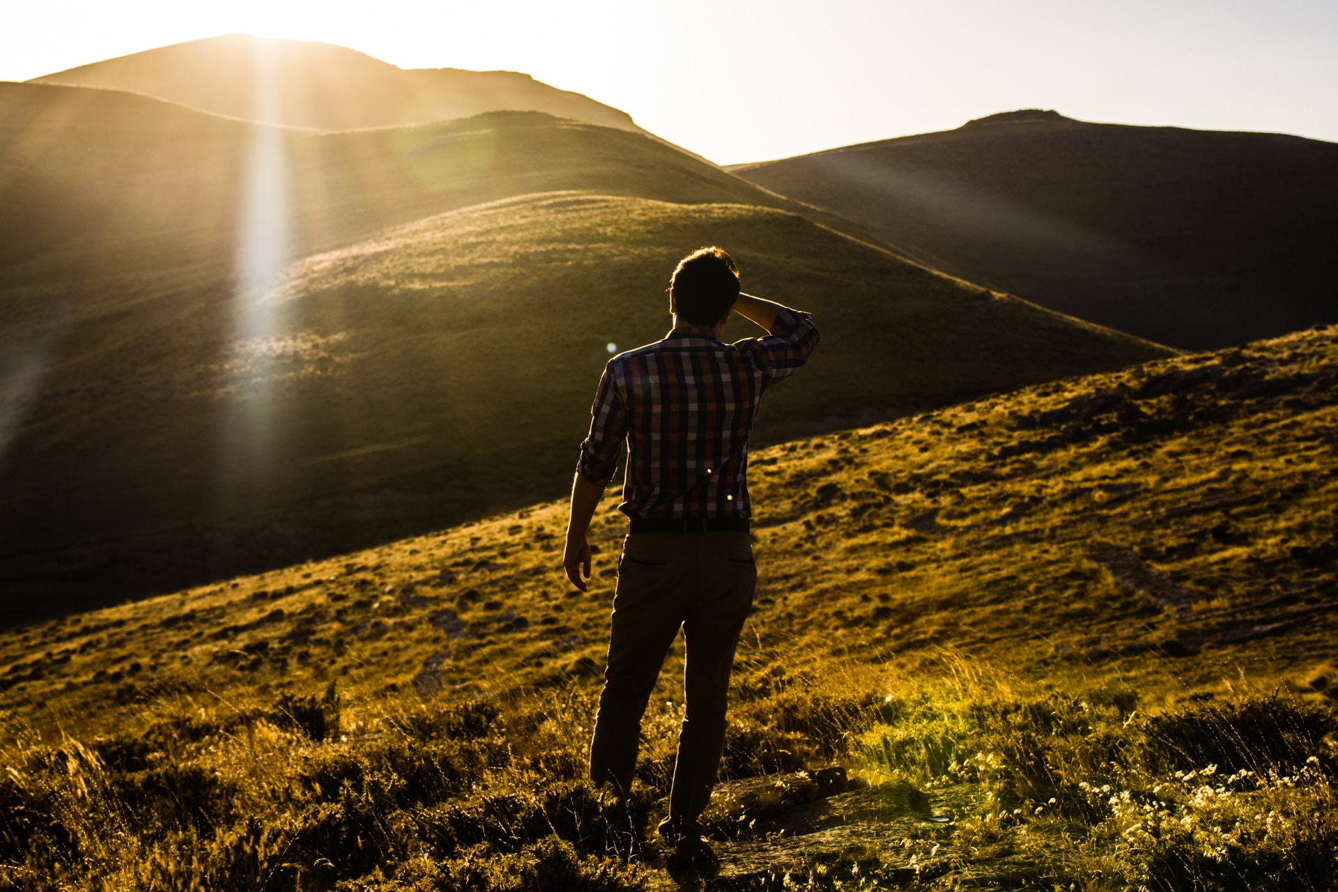 man standing on hill under white sky at daytime