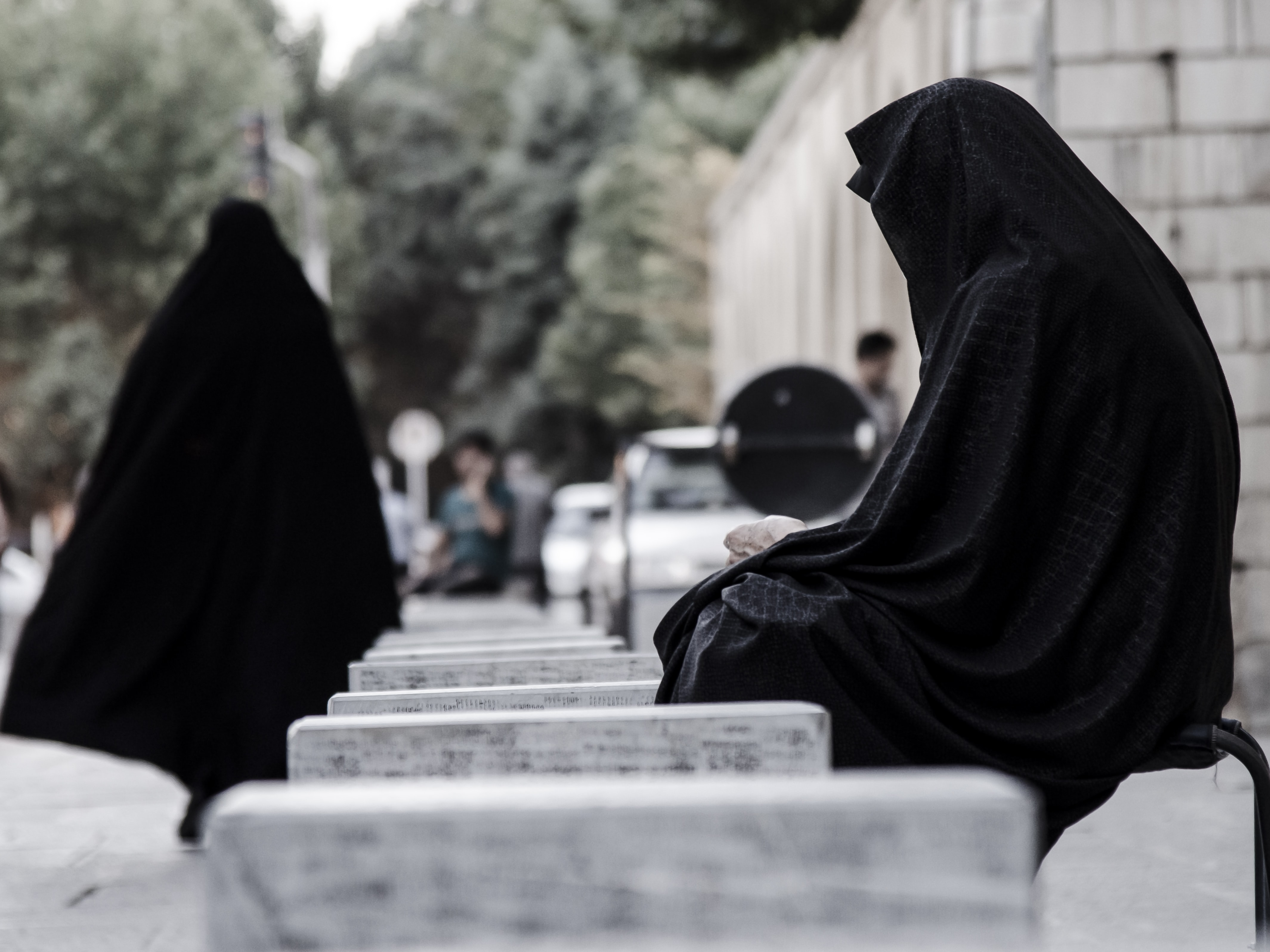 People wearing black burka outfits at a city square in Iran