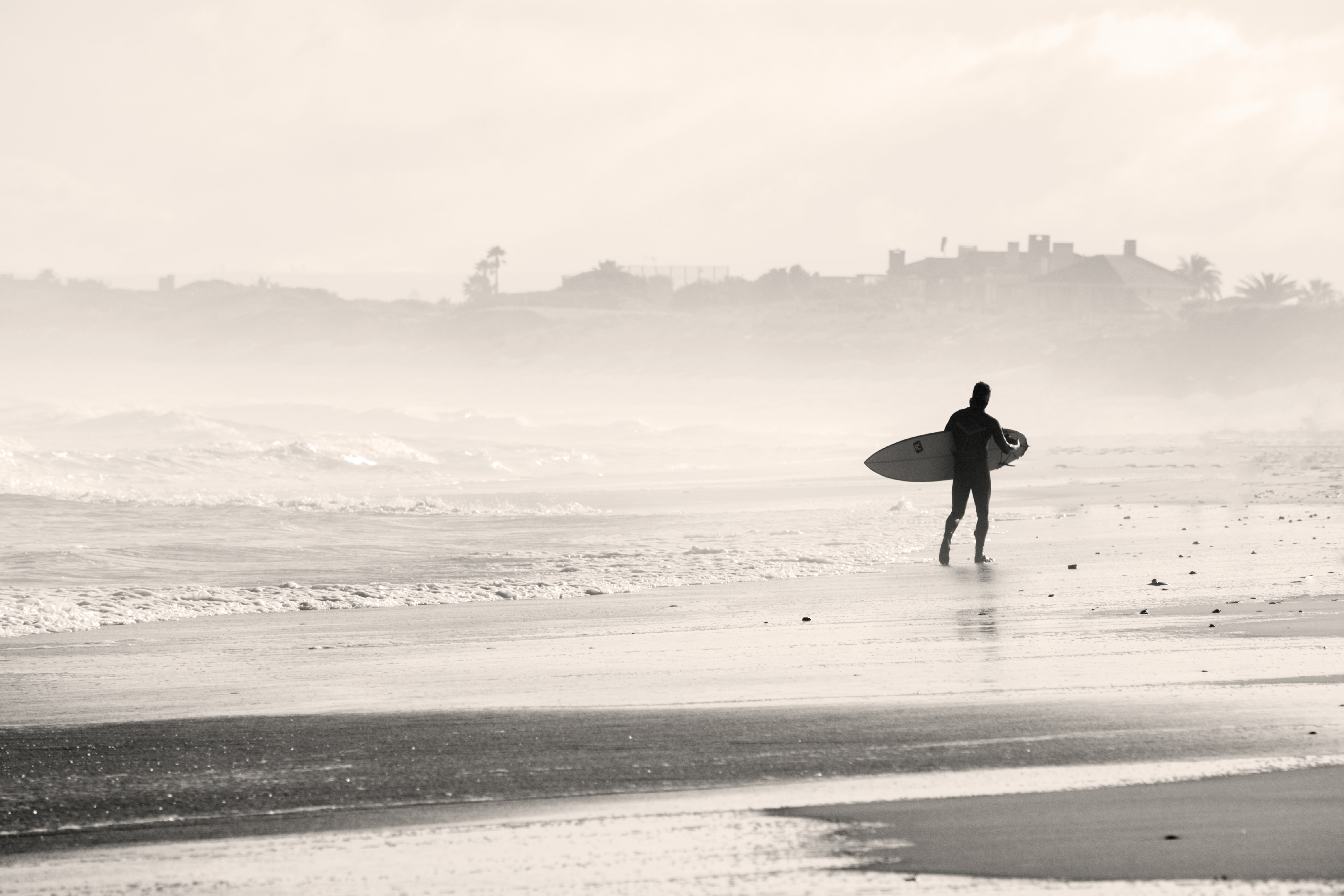 Surfer walking on the beach by the rough ocean in Cape Town