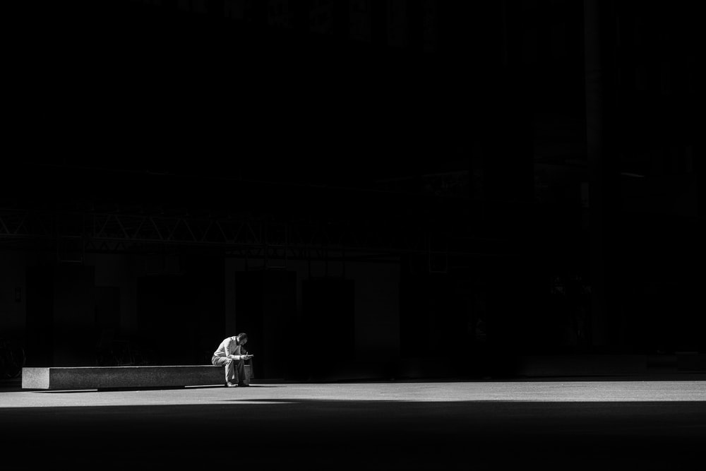 grayscale photogaphy of man sitting on concrete bench