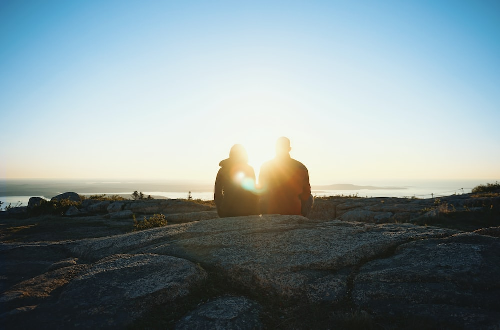 silhouette of two person during sunrise