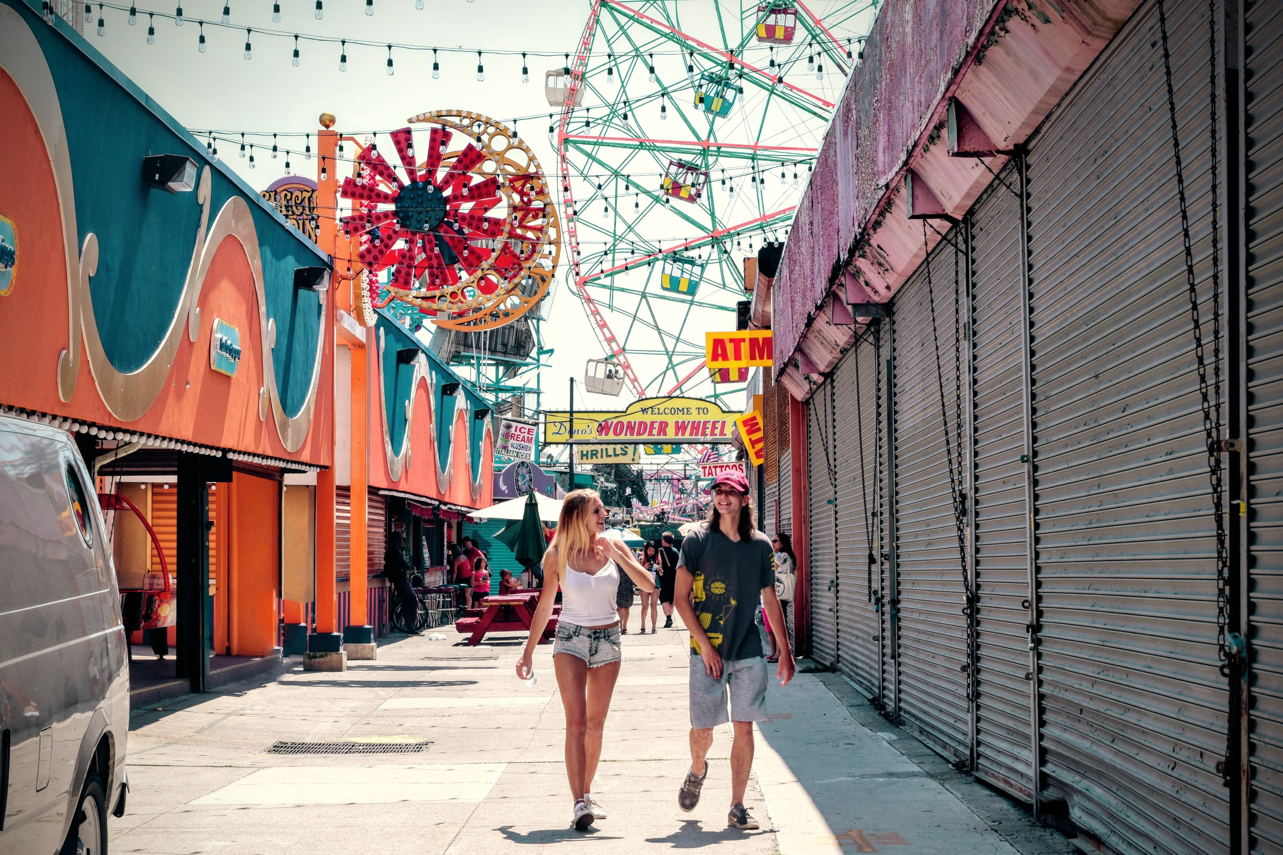 A couple walking down the boardwalk at Coney Island with the Ferris wheel and lights behind them