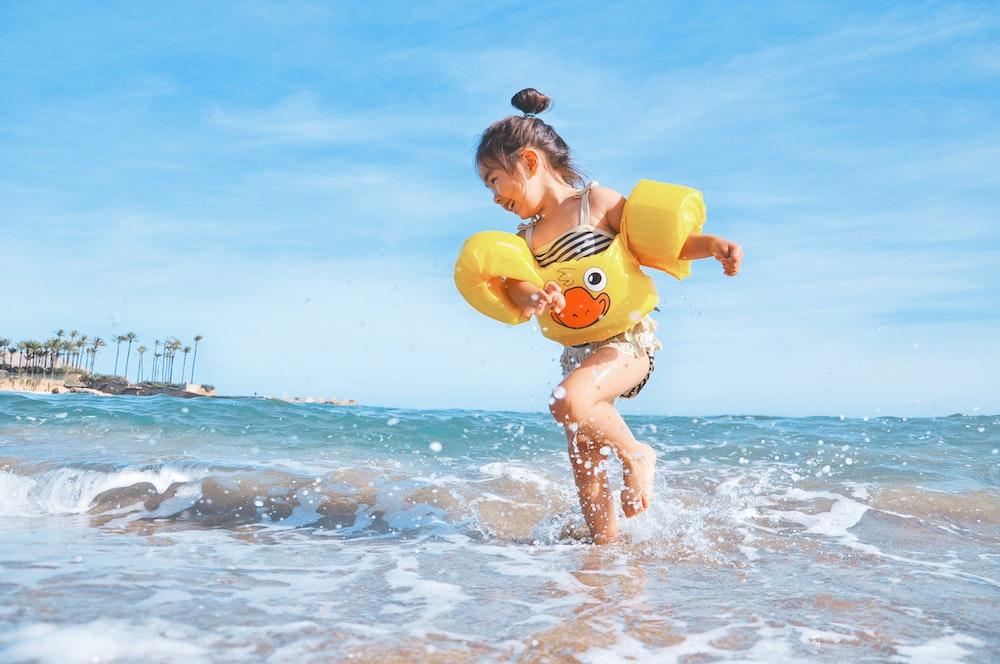 girl playing beside body of water during daytime