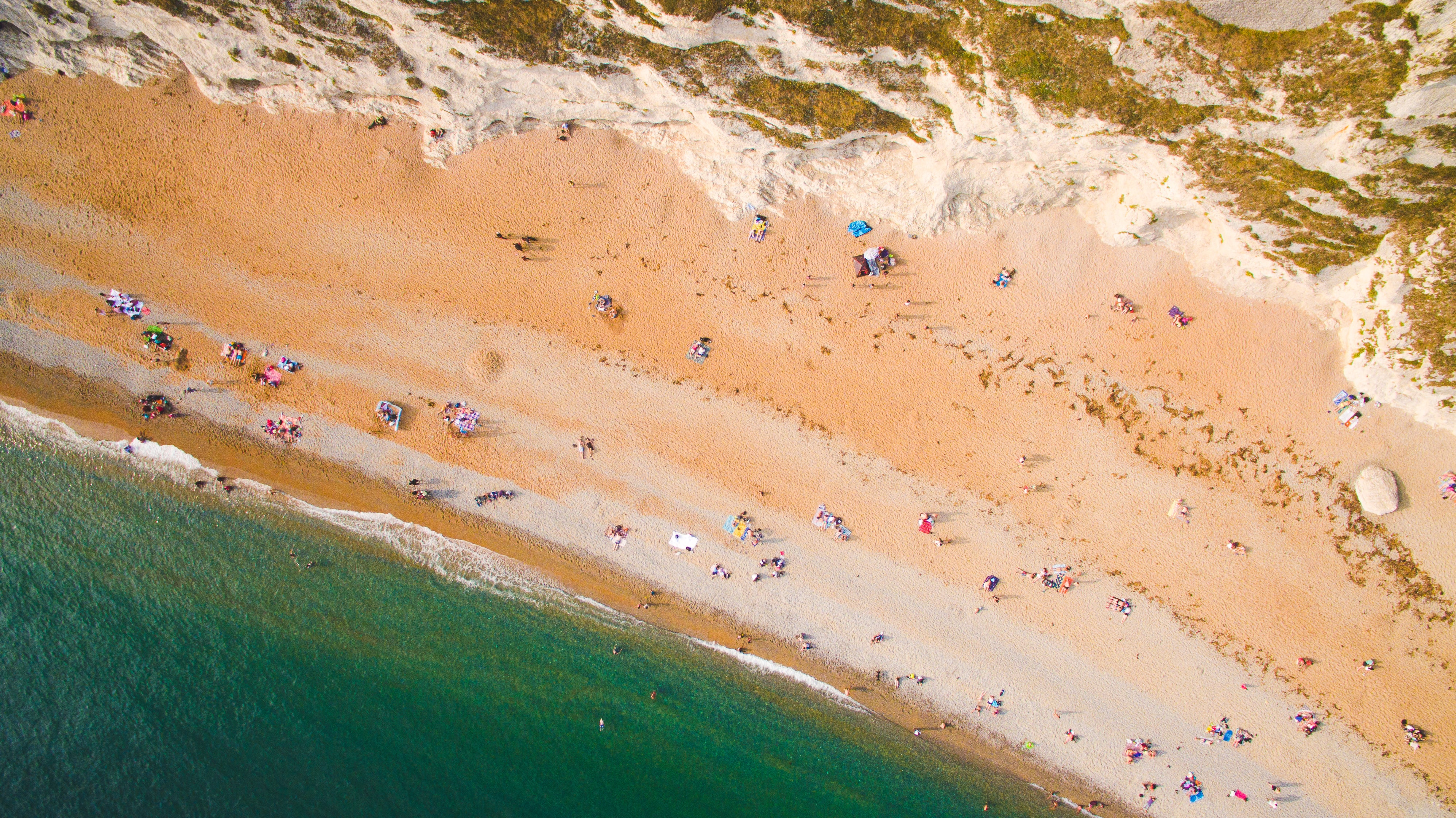 Drone aerial view of a crowded sand beach coastline at Durdle Door