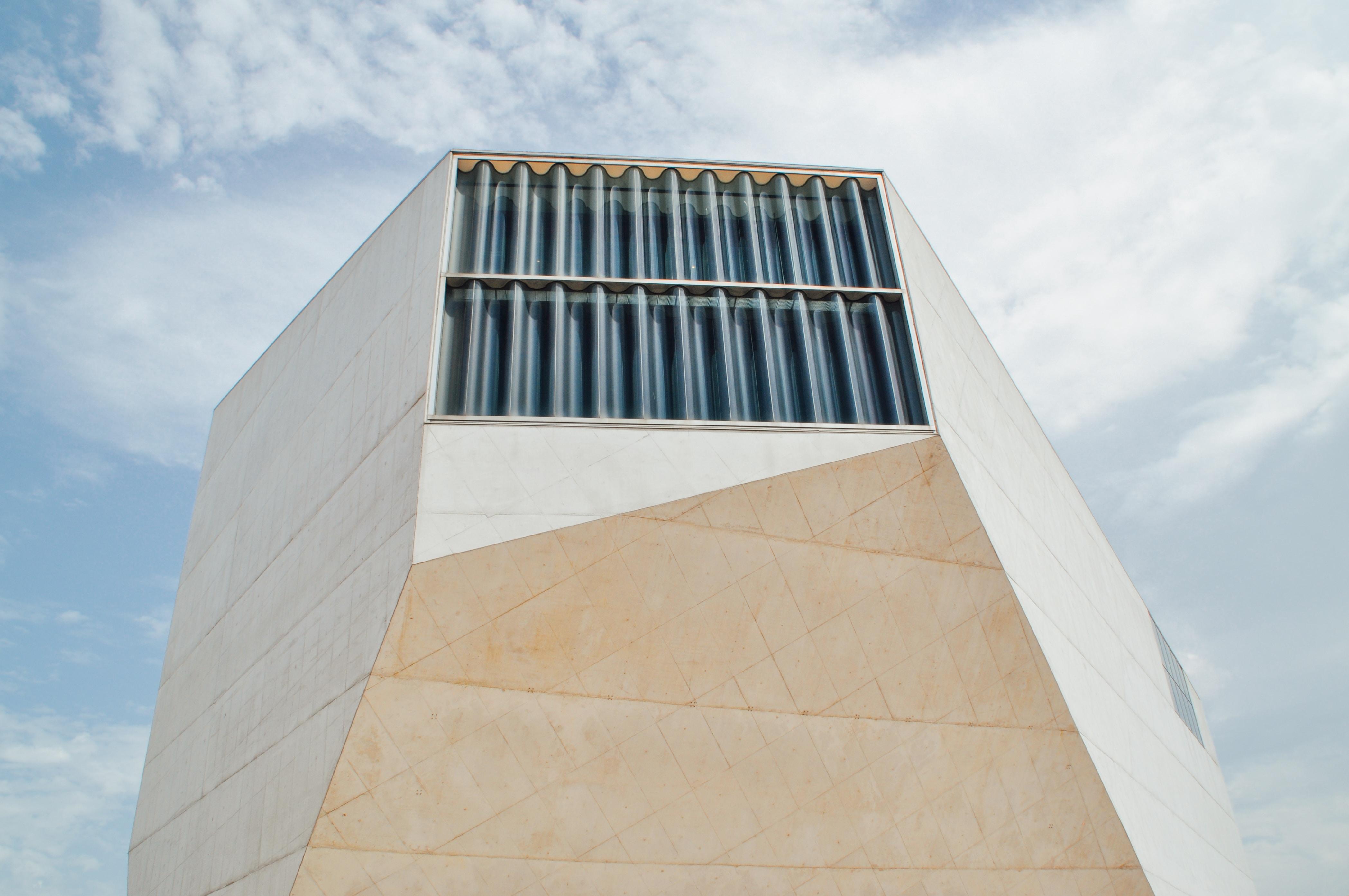 An undulating window at the top of an angular building facade