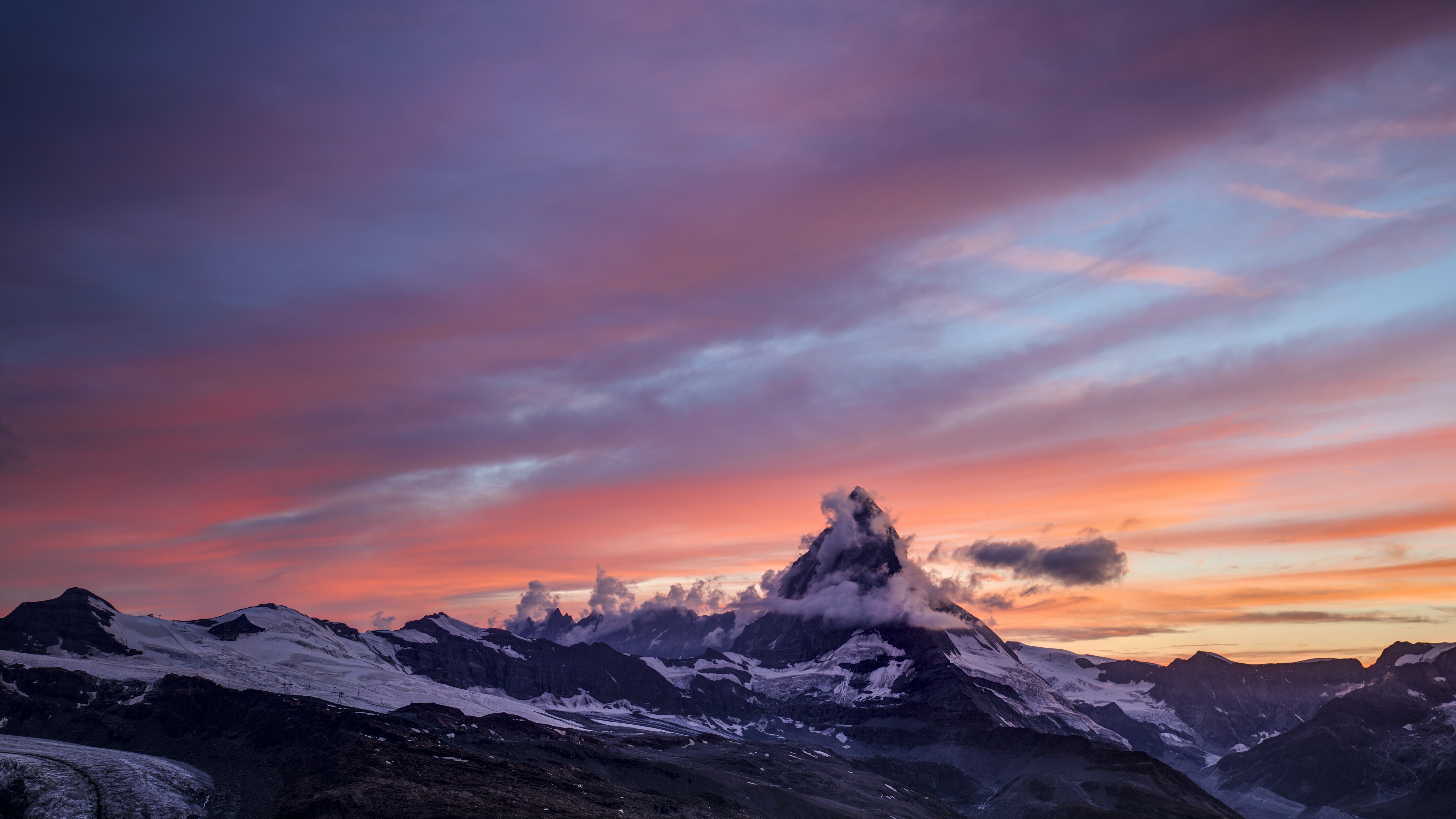 The sun setting over the snow capped Matterhorn mountain, with a blue and orange skyline