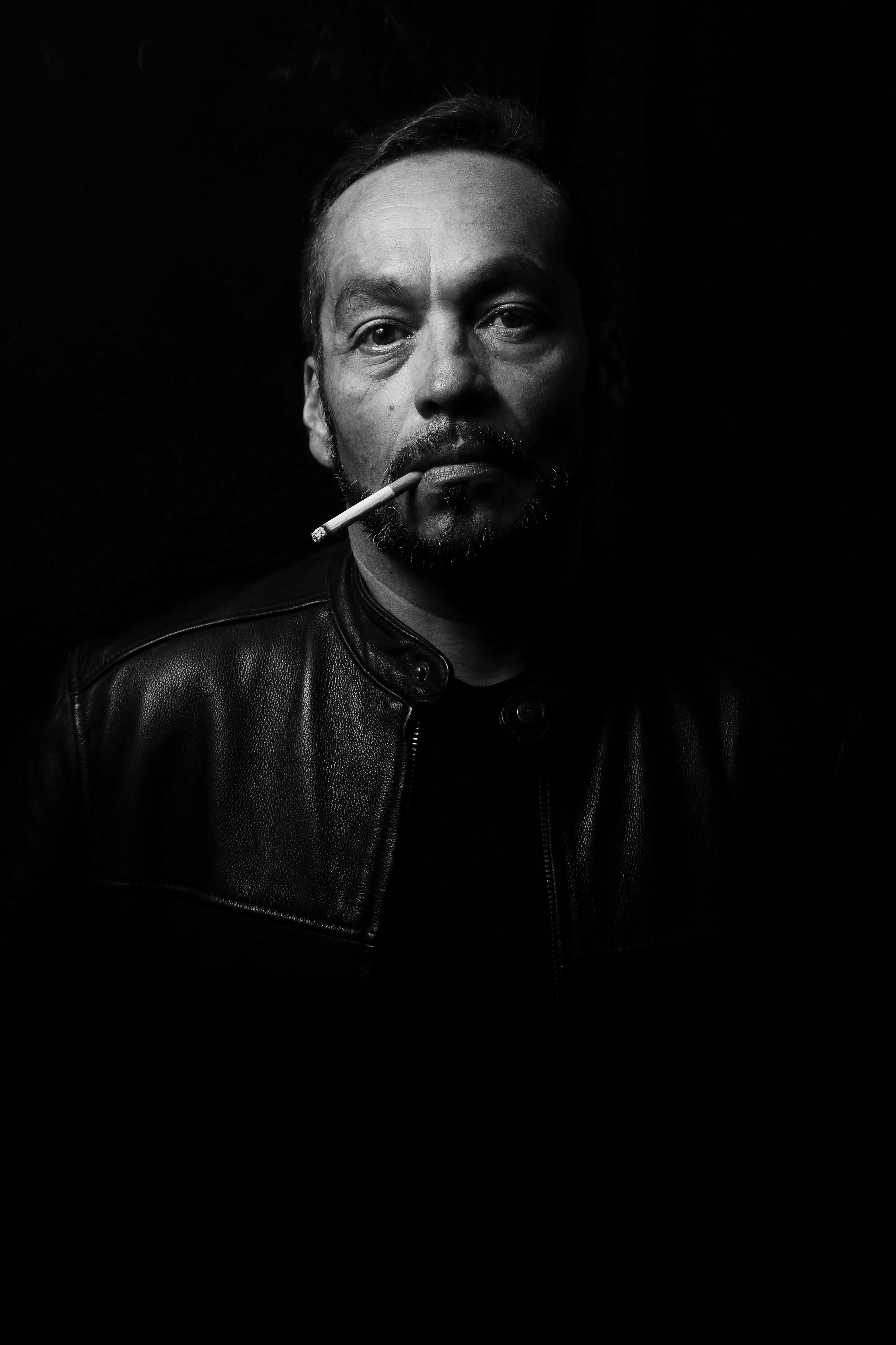 A man smoking a cigarette in the dark wearing a leather jacket in San José