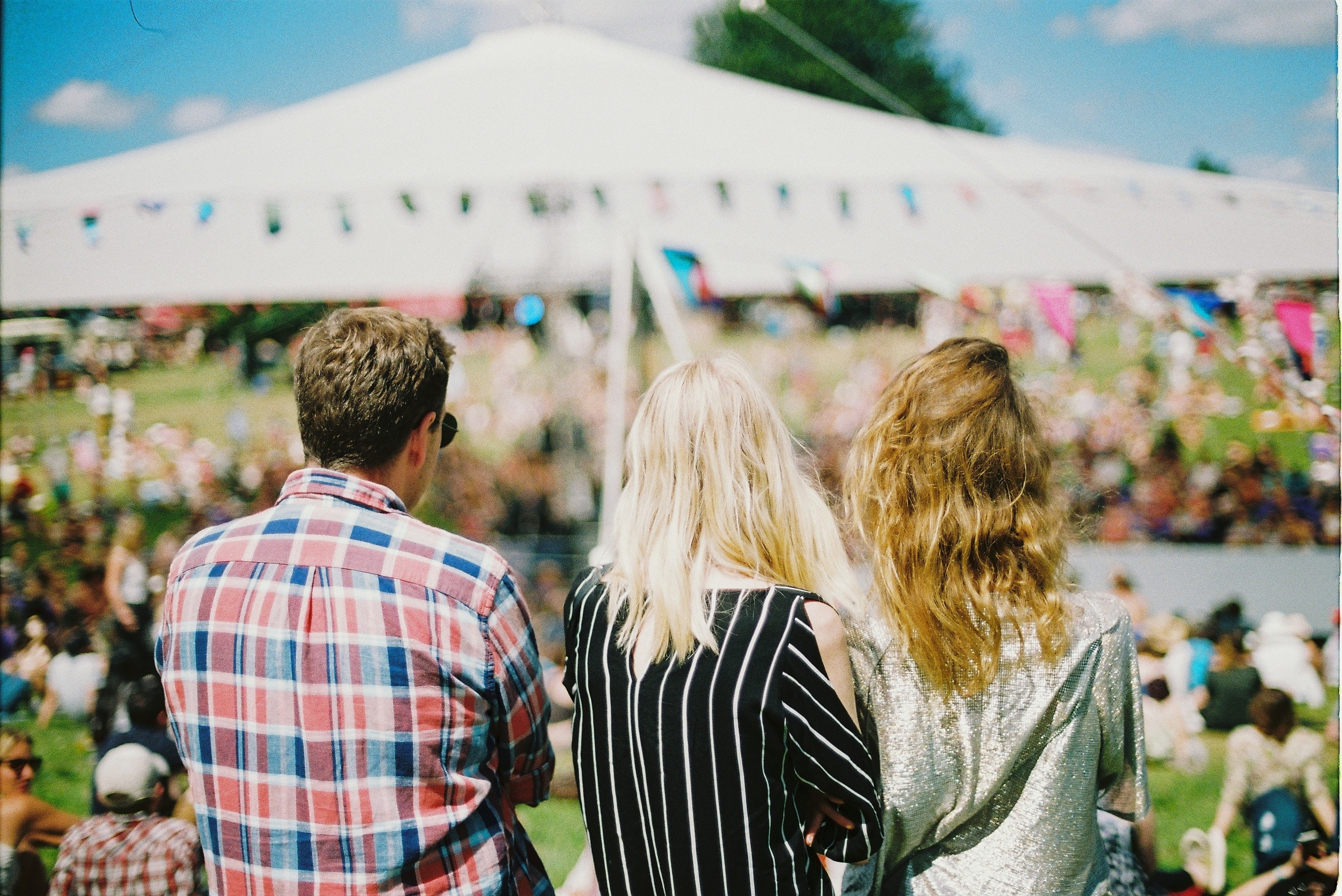 A man and two women standing back to camera at a music festival