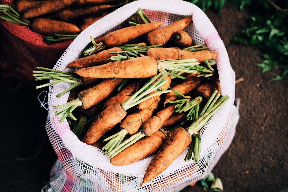 ripe carrots inside white net sack