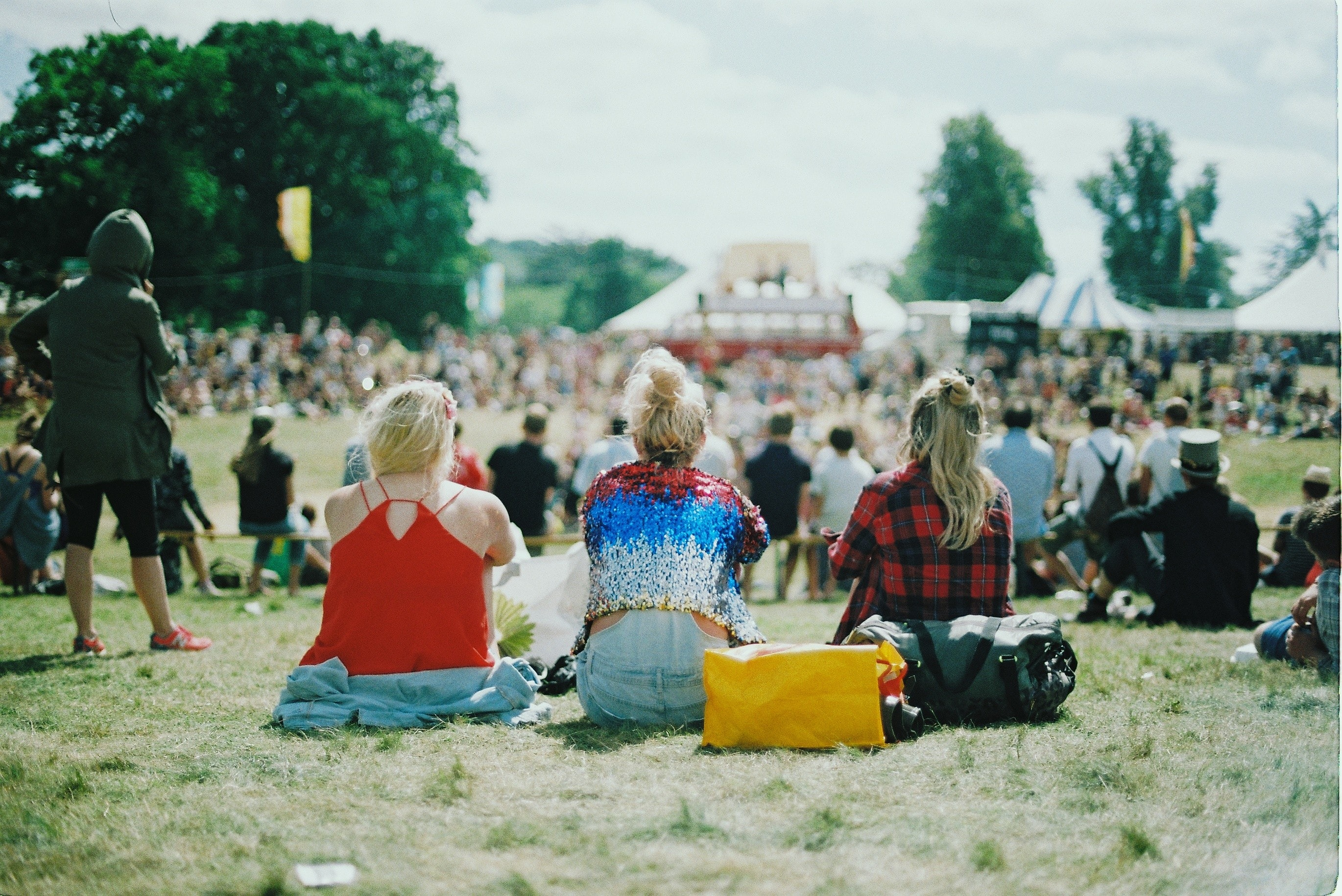 Young women sitting at the back of an audience at a music festival