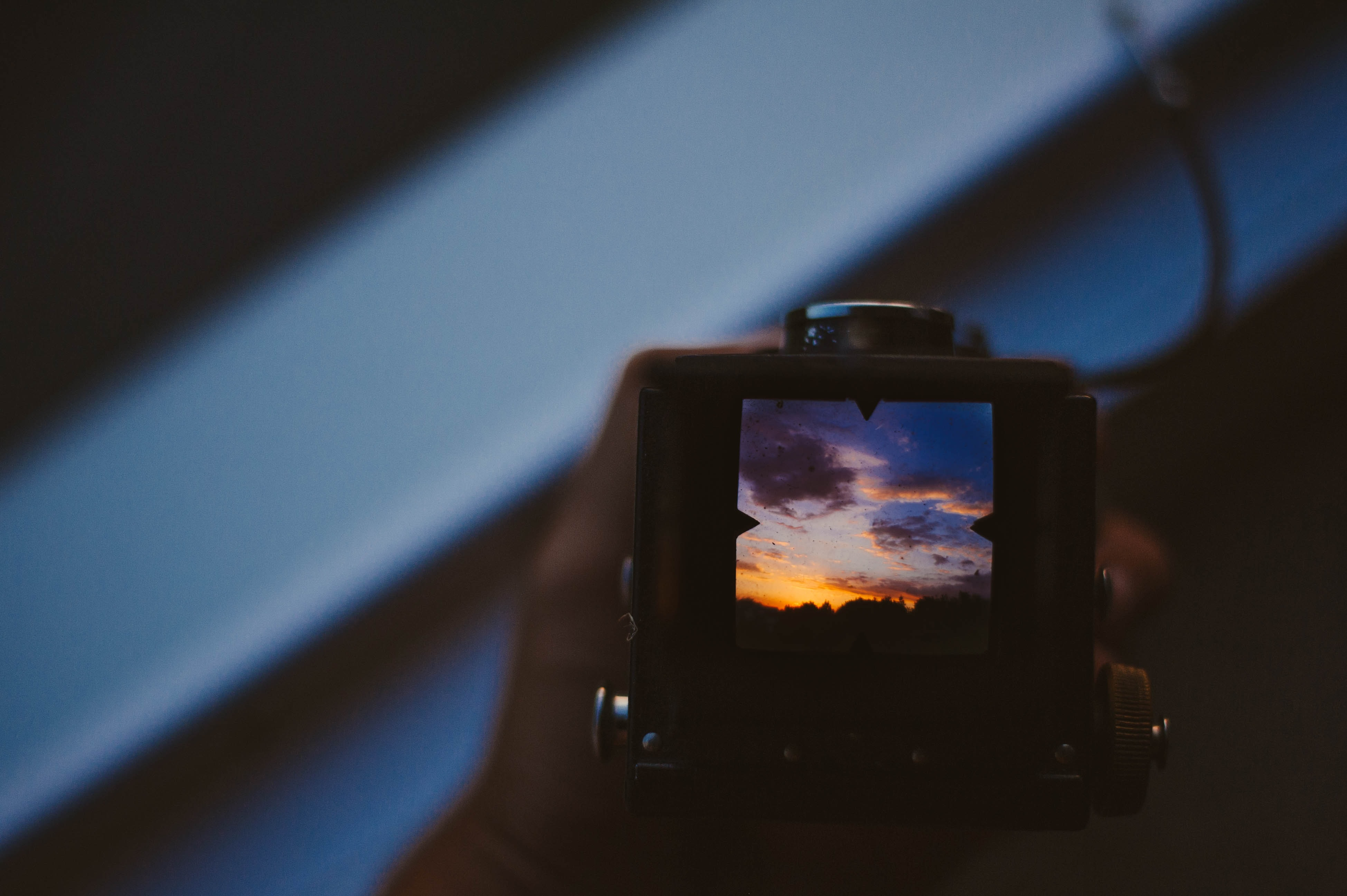 A view from behind a vintage camera toward the viewfinder that displays a yellow and blue sunset sky