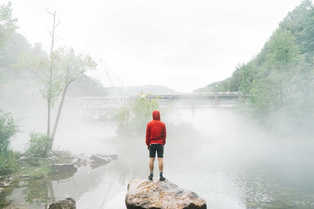 man standing on rock facing foggy creek