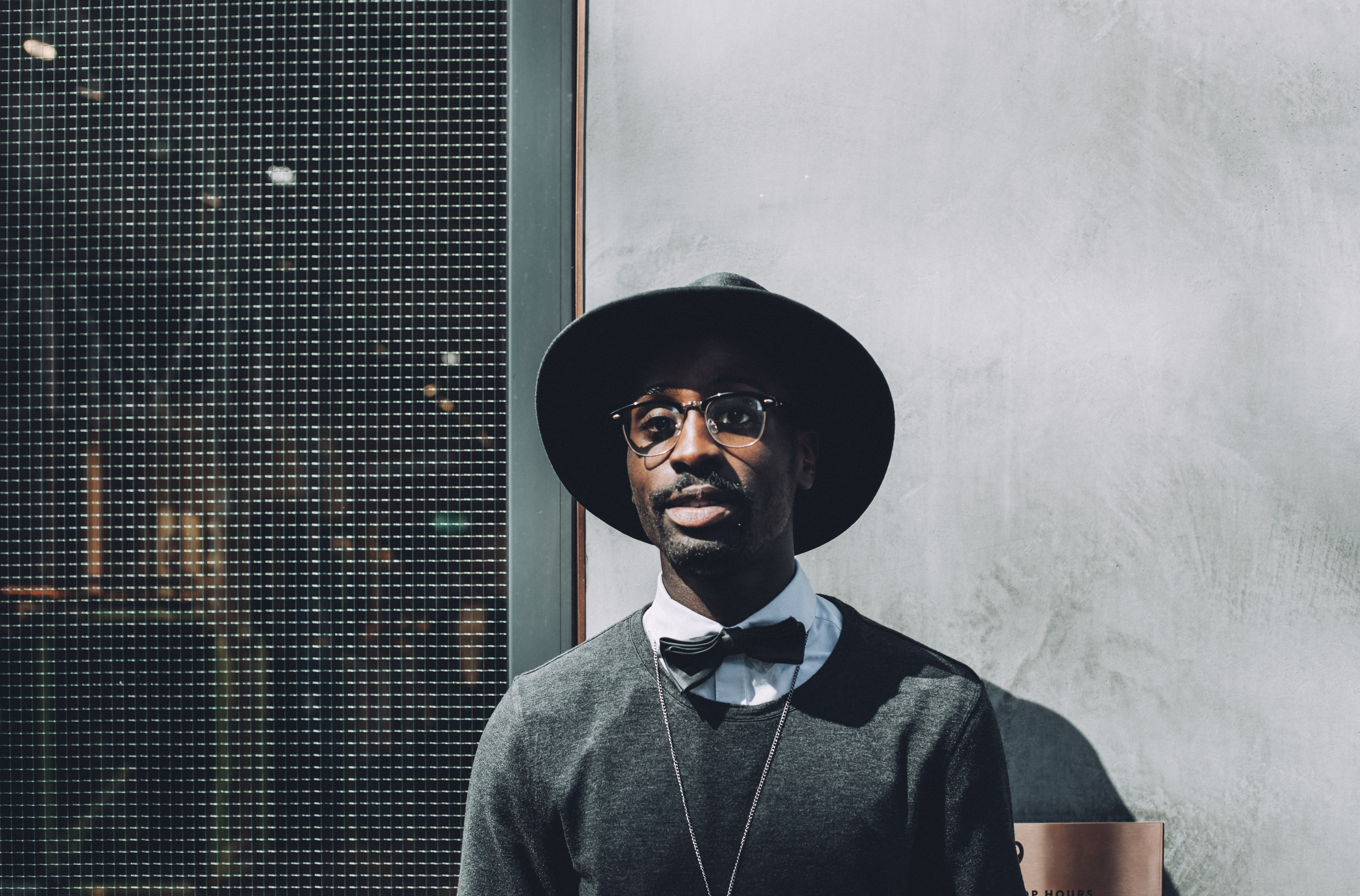 Trendy man in a hat and bow tie standing happily outside