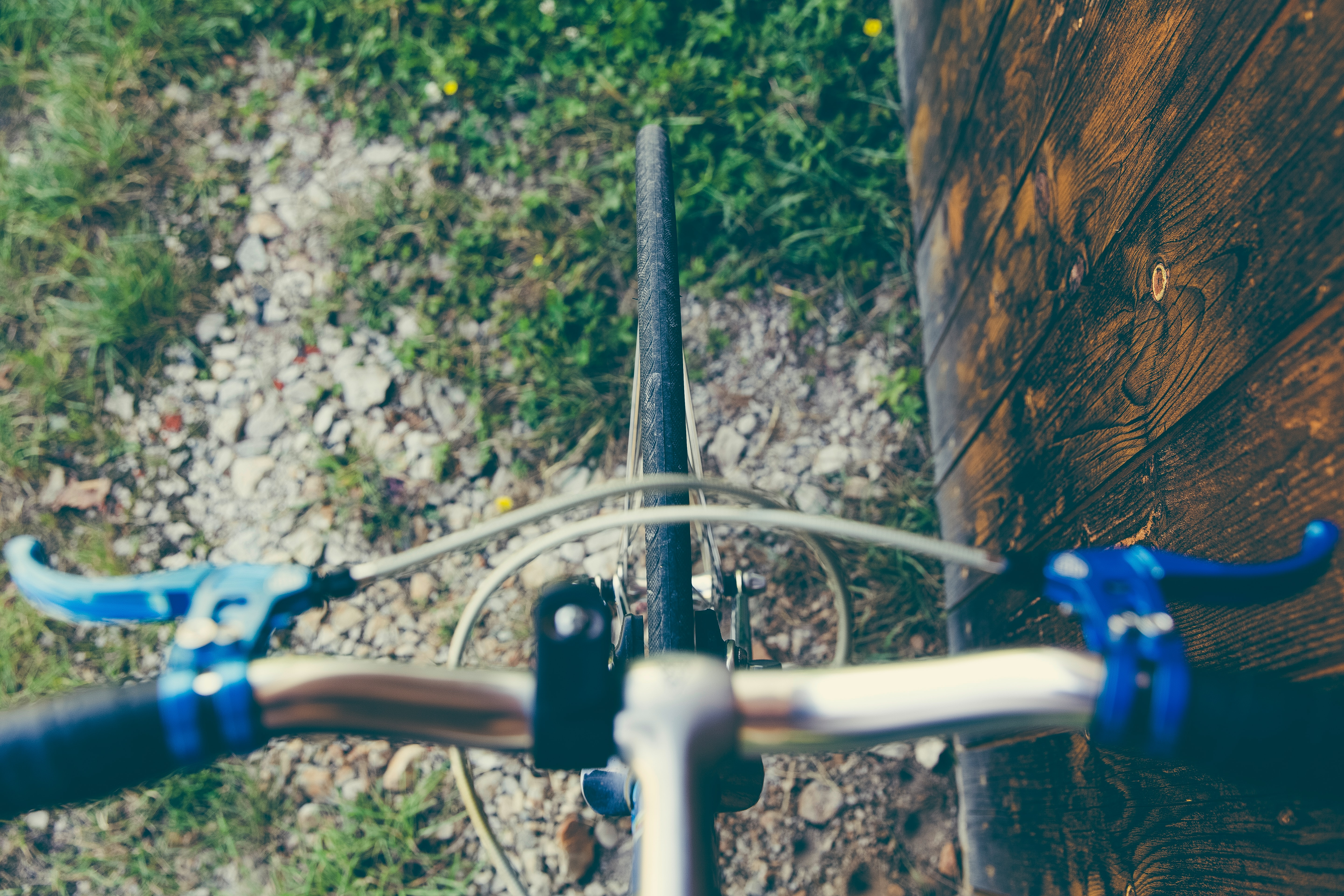 Drone view of bicycle handlebars and brakes on gravel and grass near a wall
