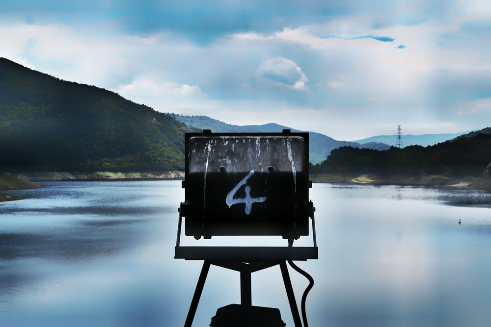 A sign marked with the number four over a lake