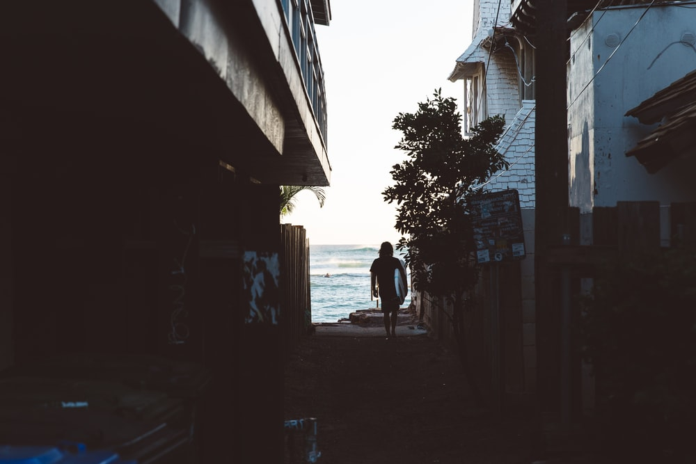 Surfer walking through the alley towards the ocean