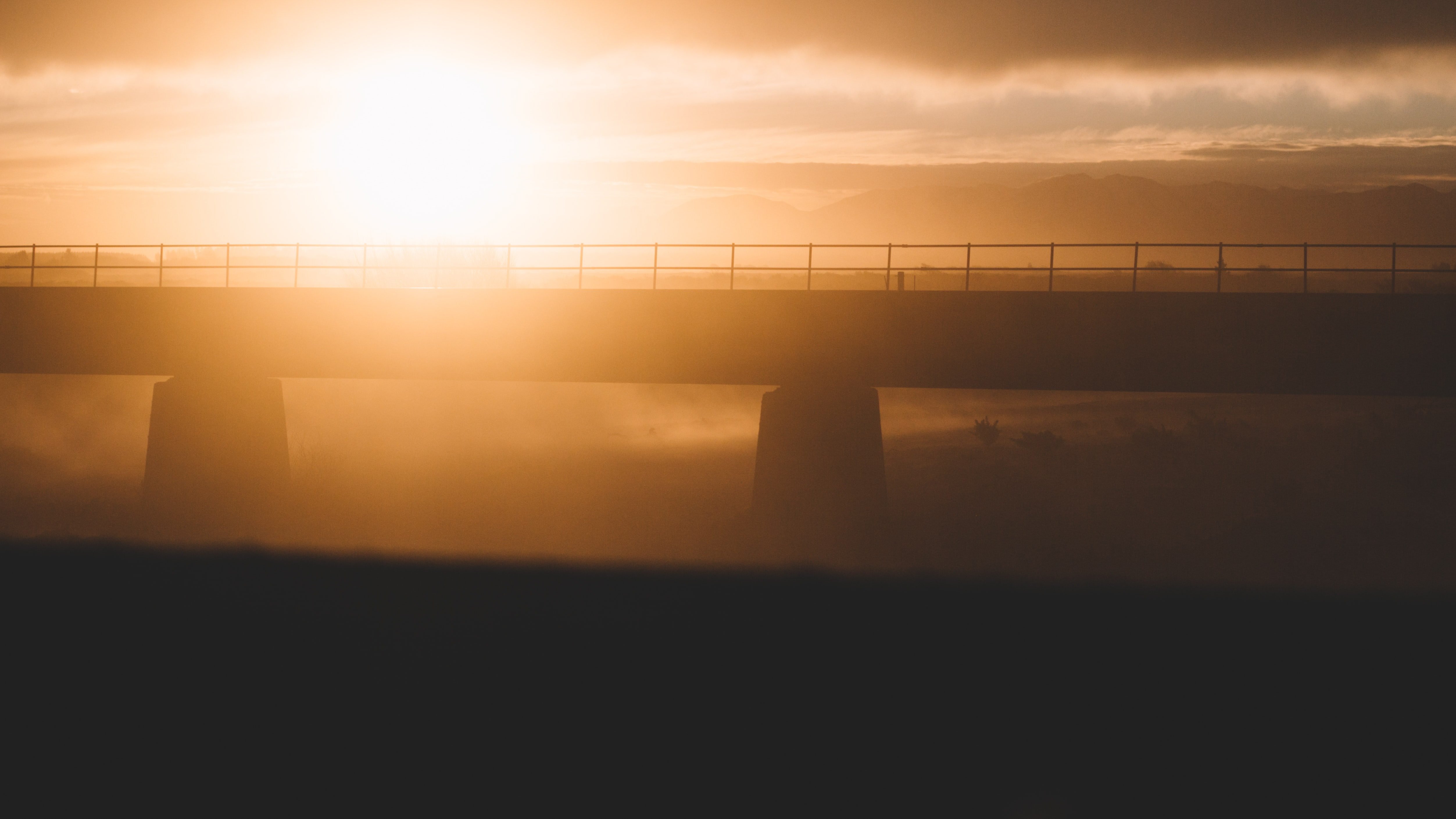 A hazy golden sunset puts a modern bridge into silhouette at Rangitata River.