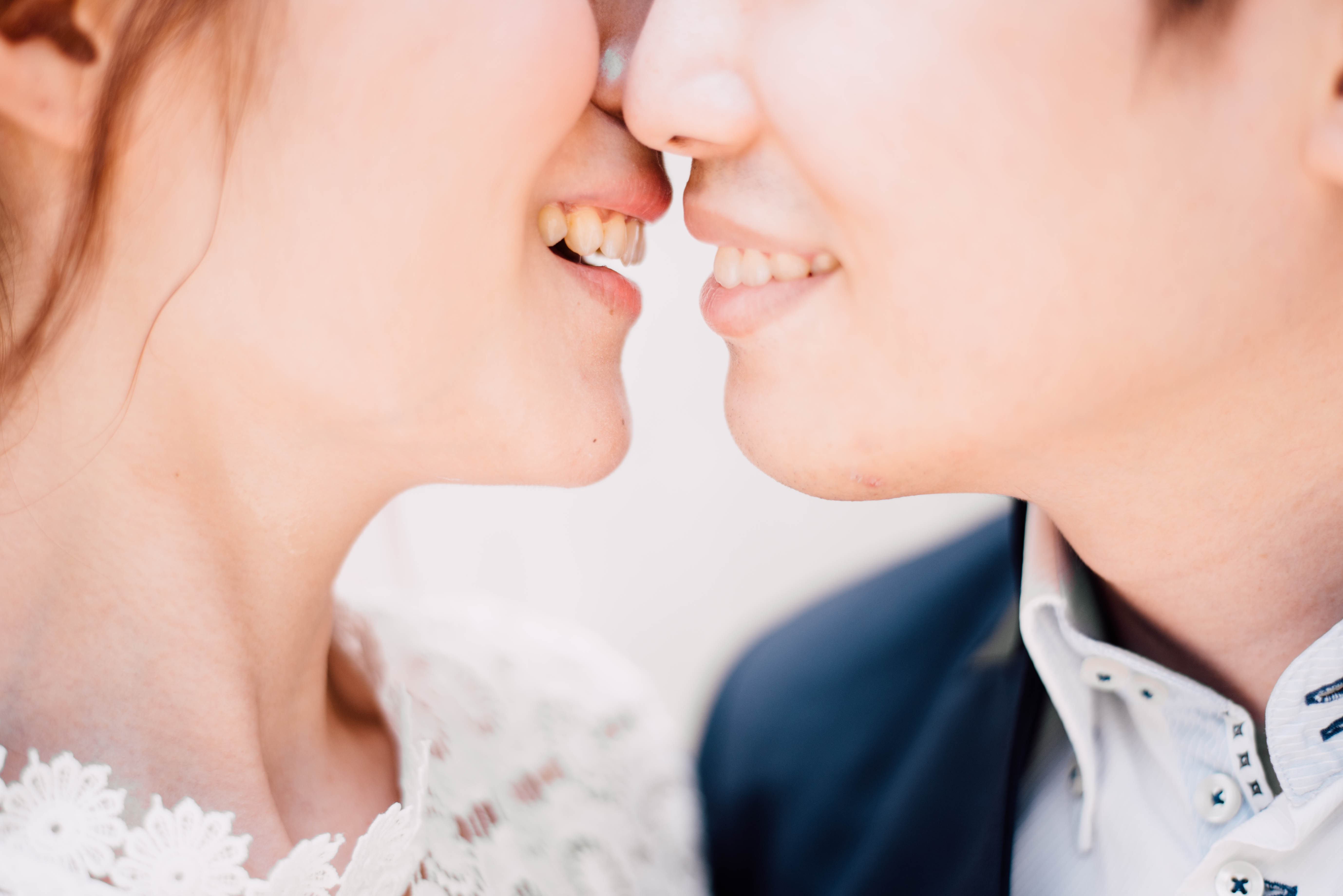 A male and female smiling while embracing for a kiss.