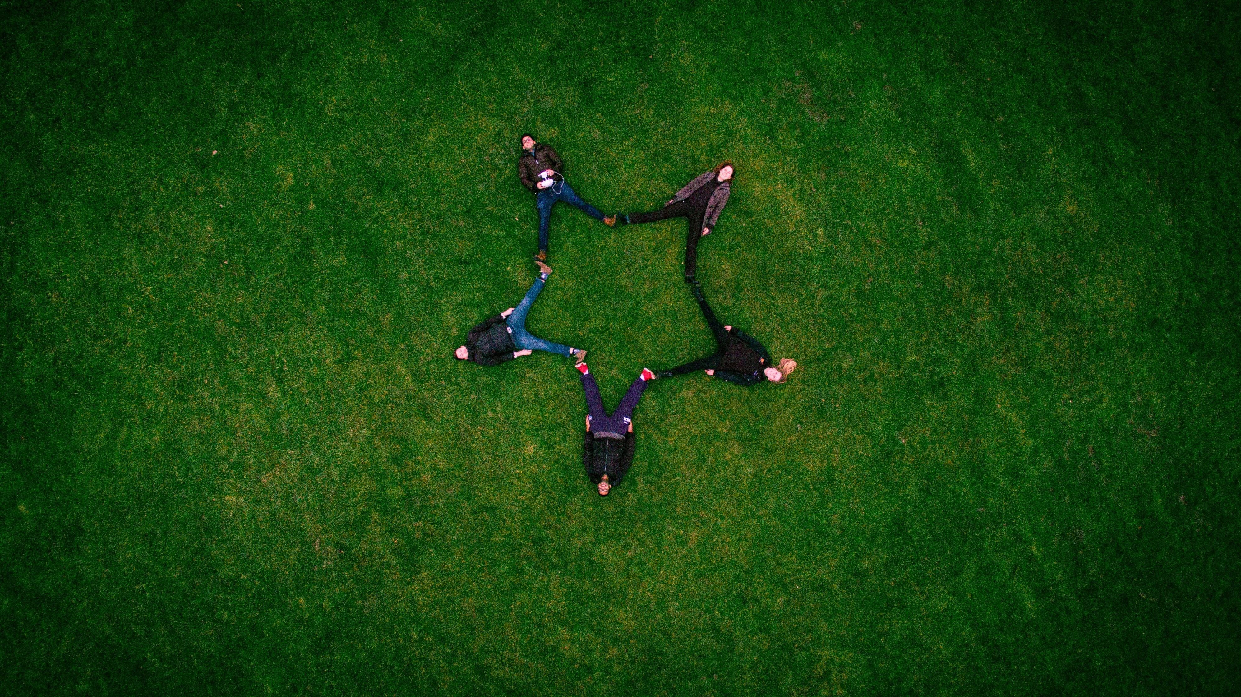five people laying on grass field making star sign