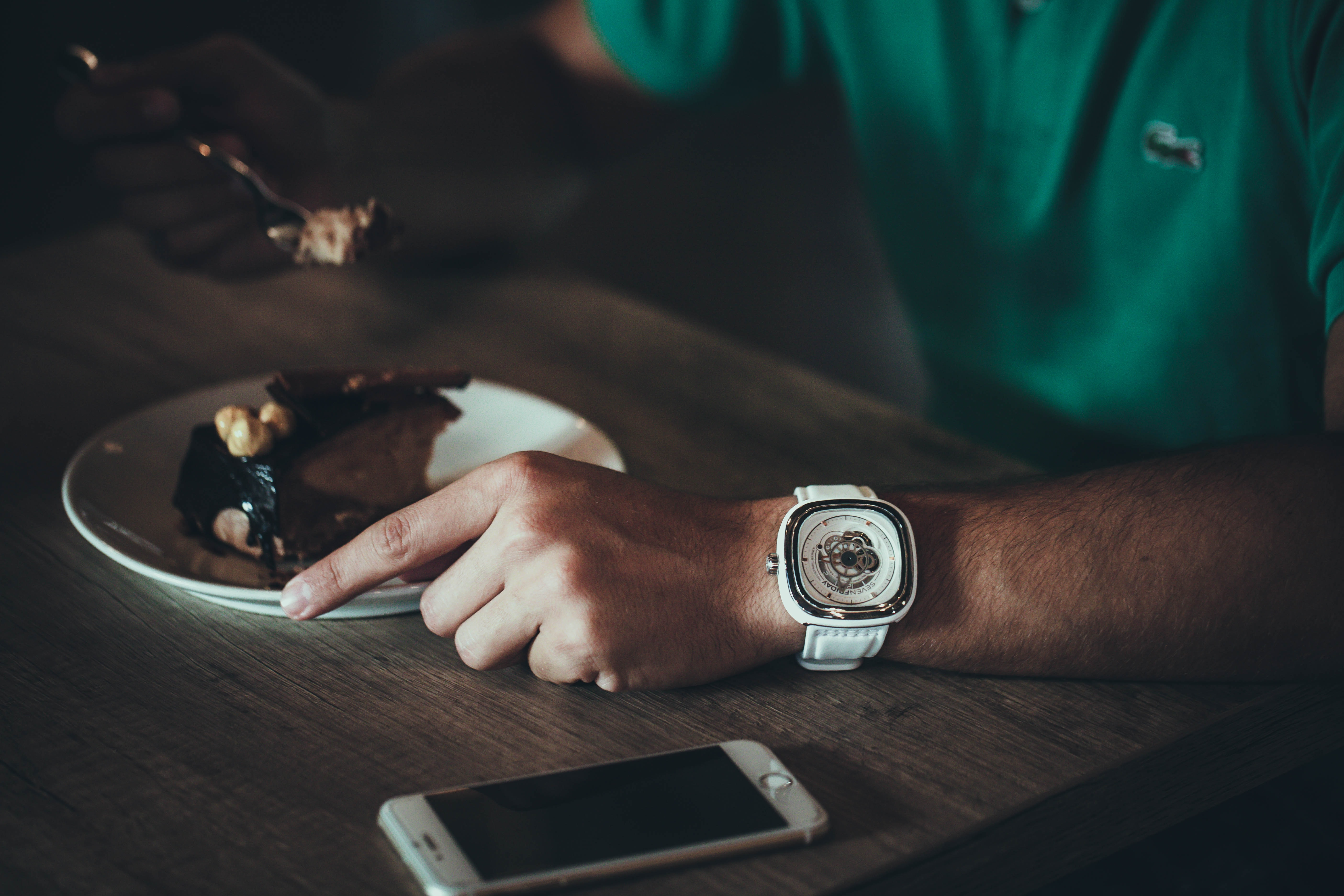 A man wearing a white watch and green shirt eating a slice of cake at a cafe while his iPhone cellphone sits nearby on the table in Switzerland