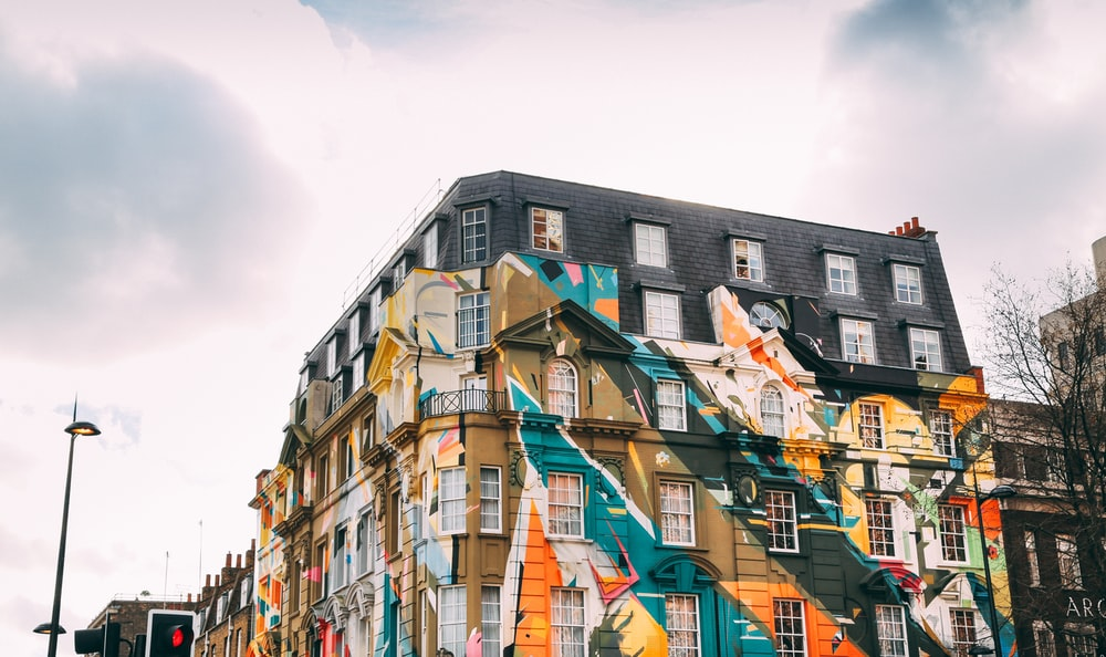 low-angle photography of building with art painting