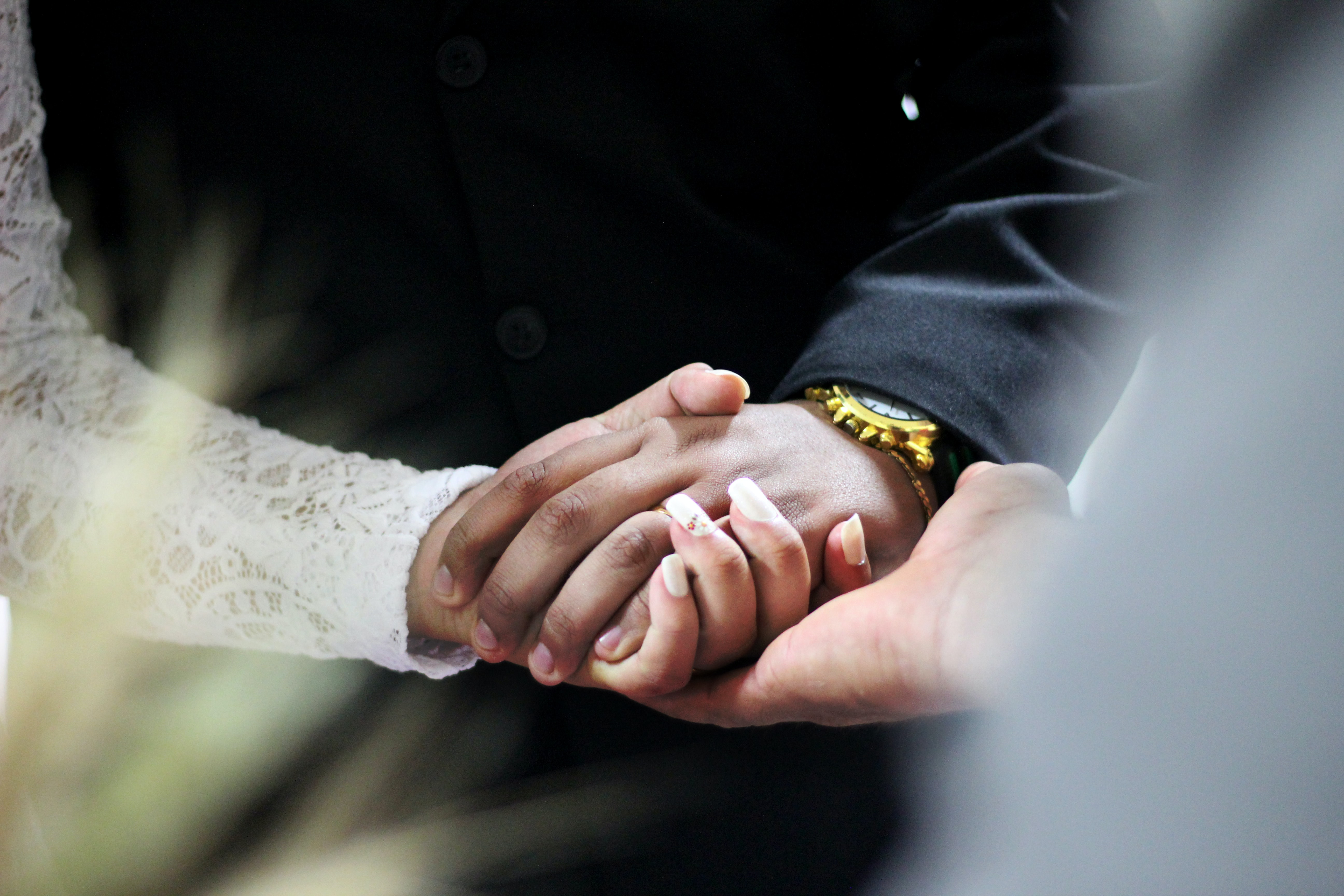 A couple holds hands as they take their vows during a wedding ceremony.