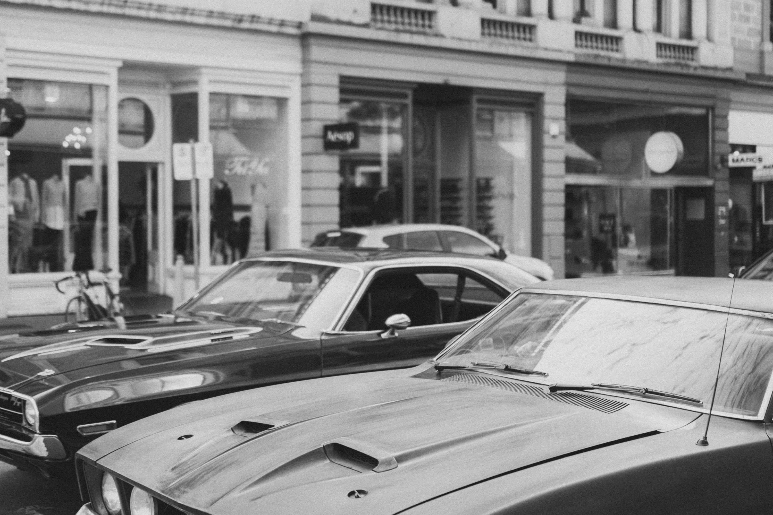 Black and white shot of two muscle cars in urban street, Rundle Street