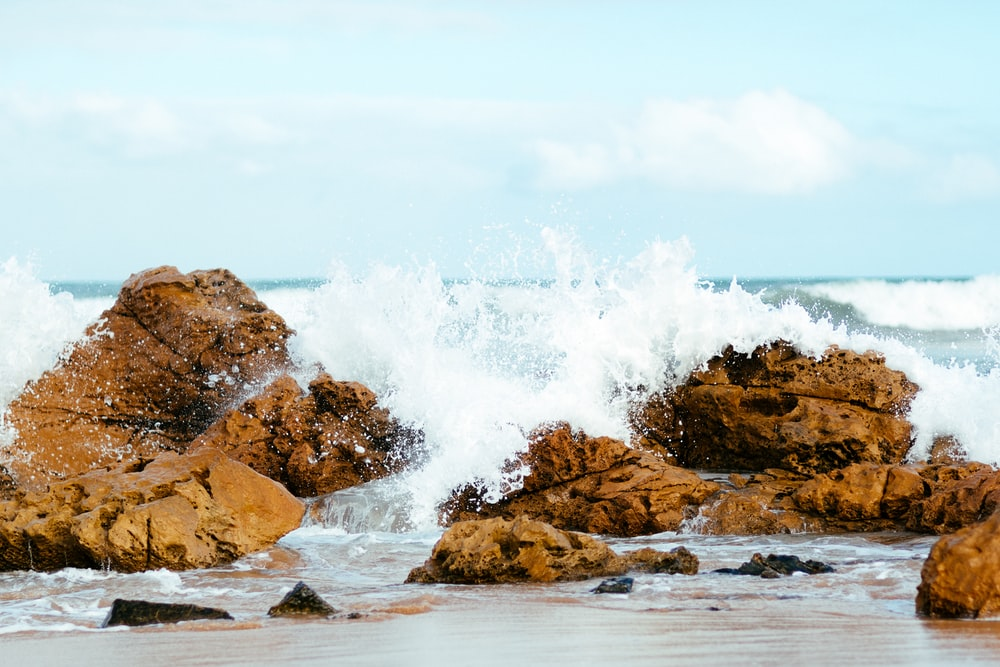 high waves crashing on rock formation at daytime